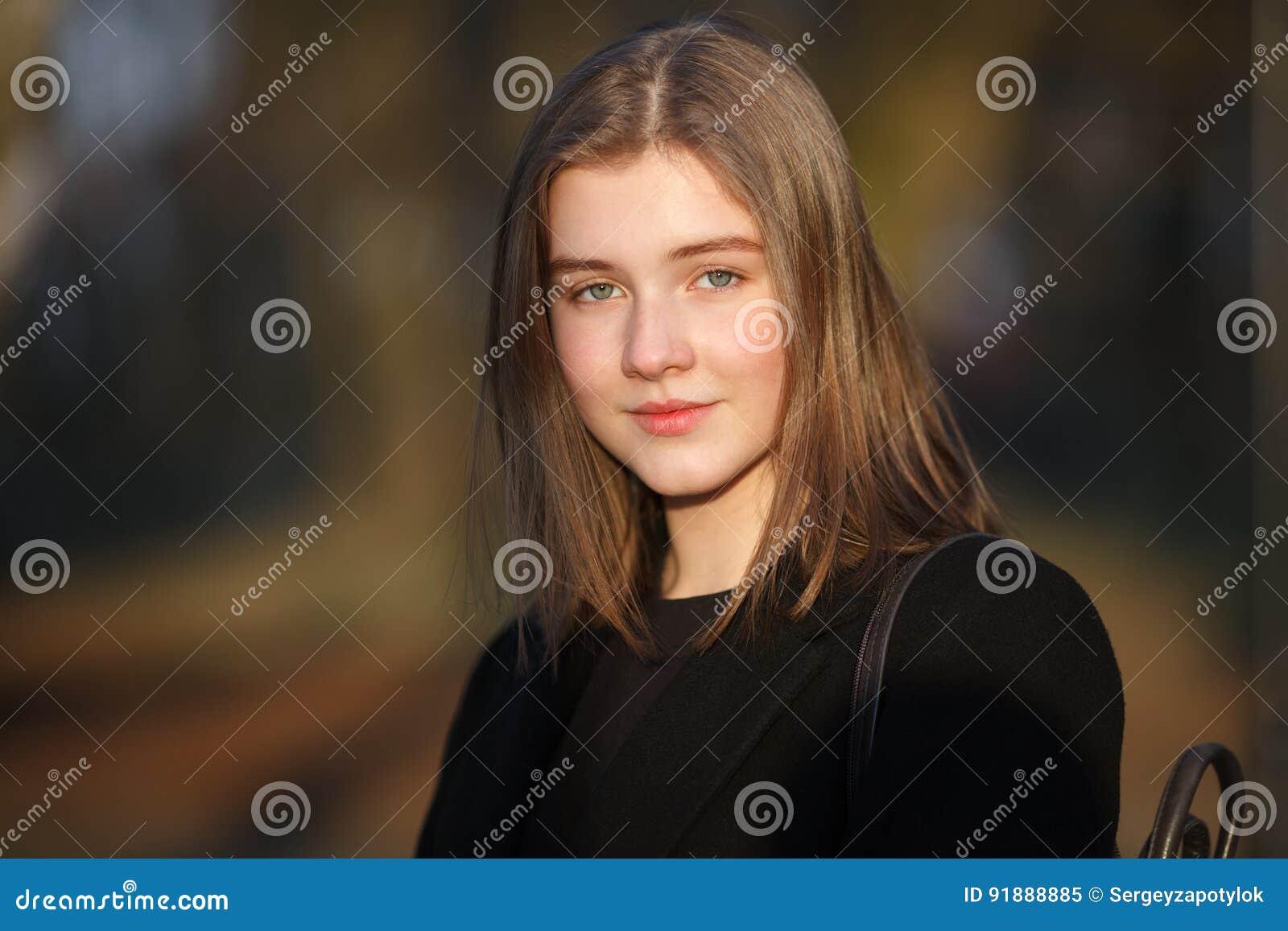 Zamyka w górę emocjonalnego portreta młoda szczęśliwa piękna kobieta jest ubranym czarnego żakiet pozuje przy evening złotą godzi