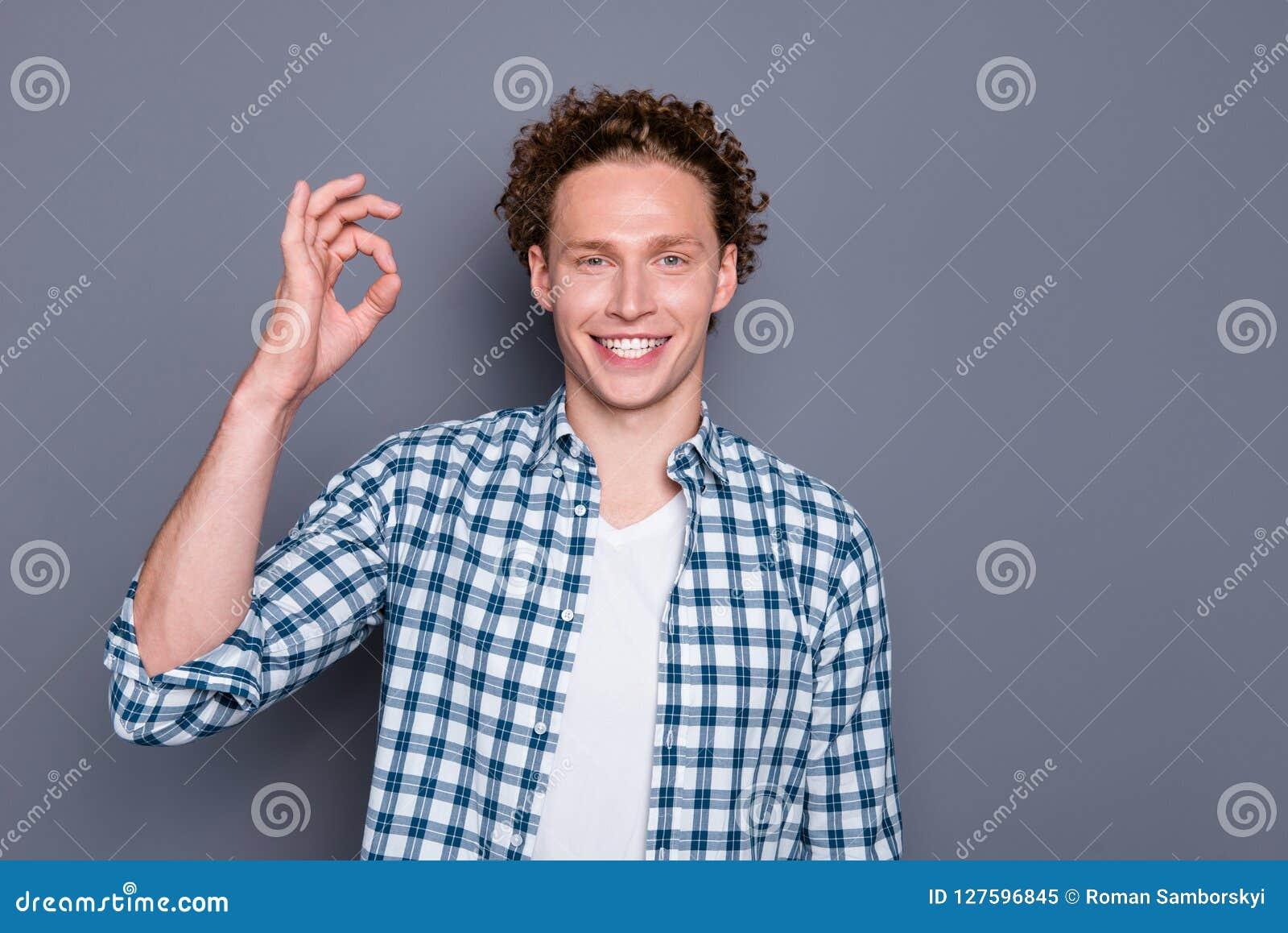 Zamyka w górę fotografia portret ofsatisfied chłodno przystojnego faceta robi ok symbolowi popielatemu tłu