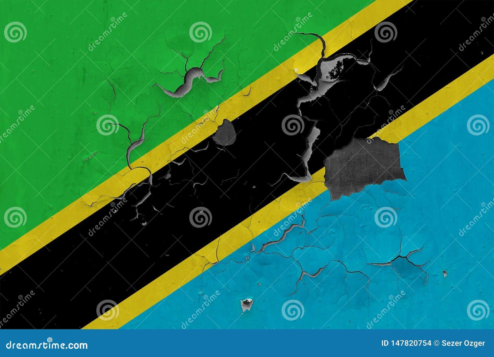 Zamyka w górę grungy, uszkadzającej i wietrzejącej Tanzania flagi na ścianie struga daleko farbę widzieć wśrodku powierzchni,
