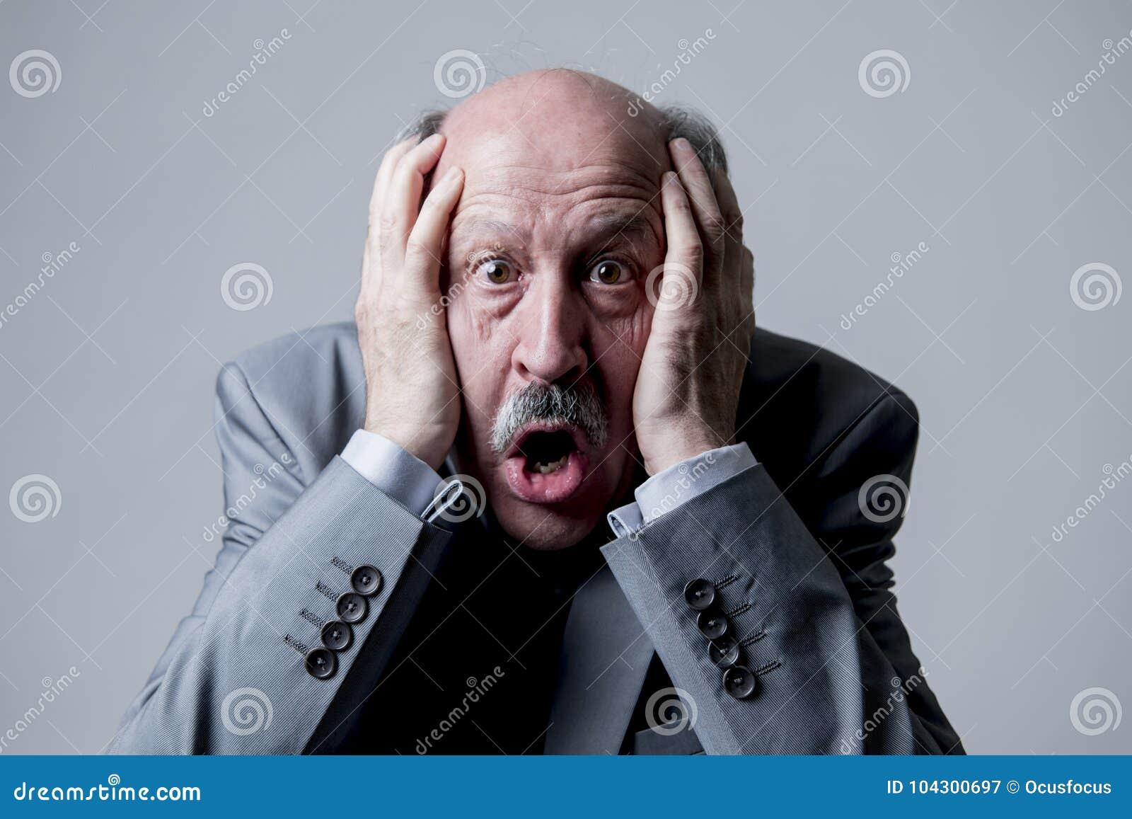 Zamyka w górę kierowniczego portreta łysy 60s starszy biznesowy mężczyzna zaskakujący i okaleczał patrzeć tak jakby duża katastro