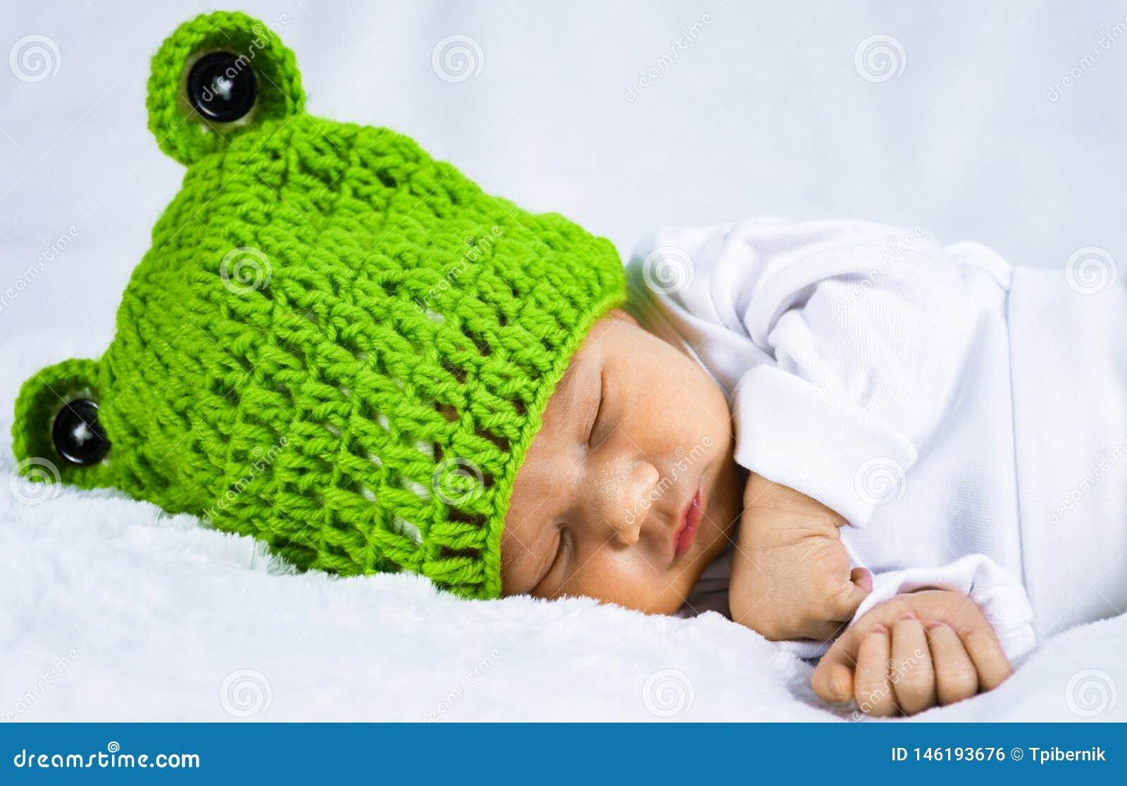Zamyka w górę kierowniczej fotografii śliczny szczęśliwy patrzeje uroczy nowonarodzony dziecko z zieloną nakrętką
