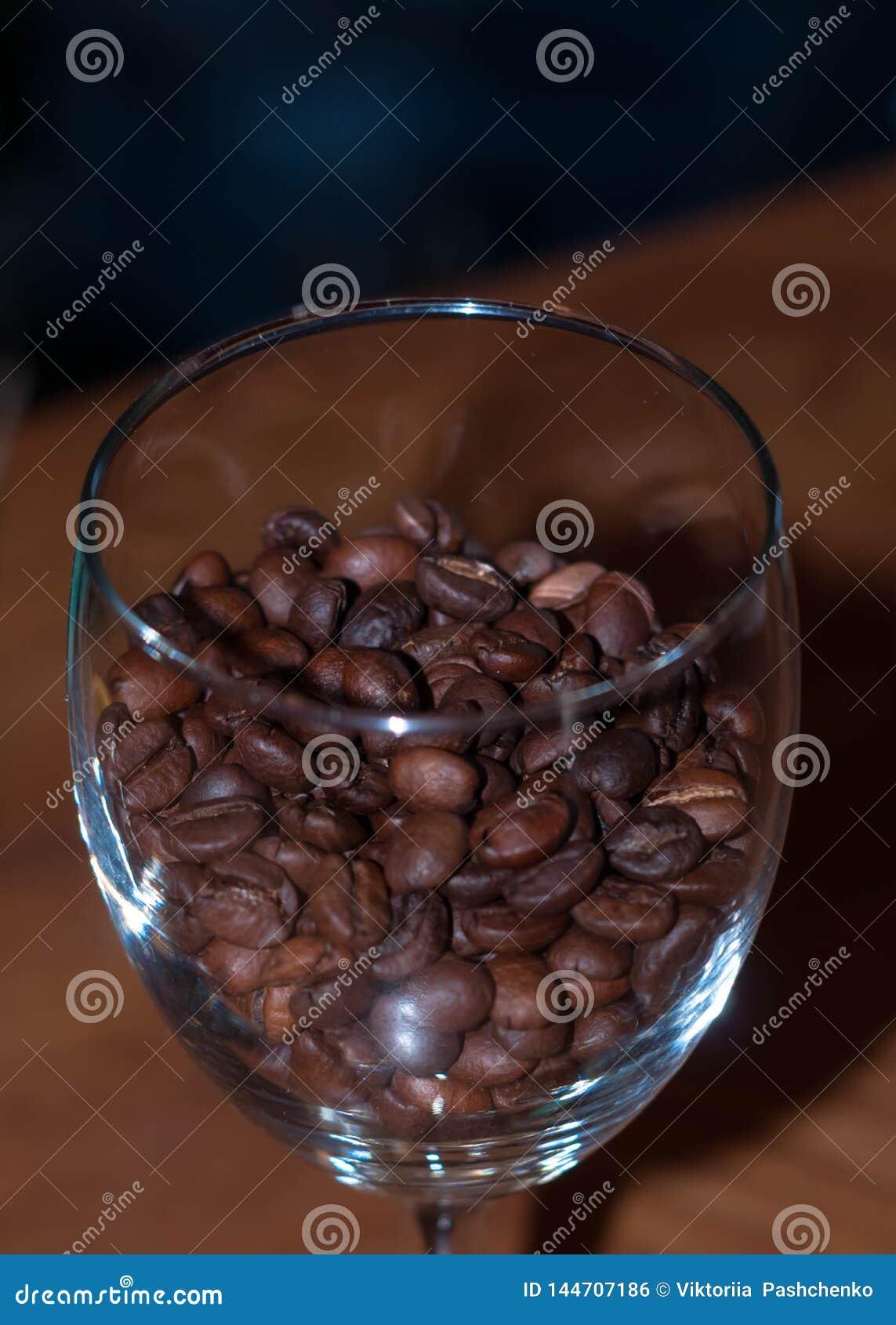Zamyka w górę krystalicznego wina szkła z brąz kawowymi fasolami