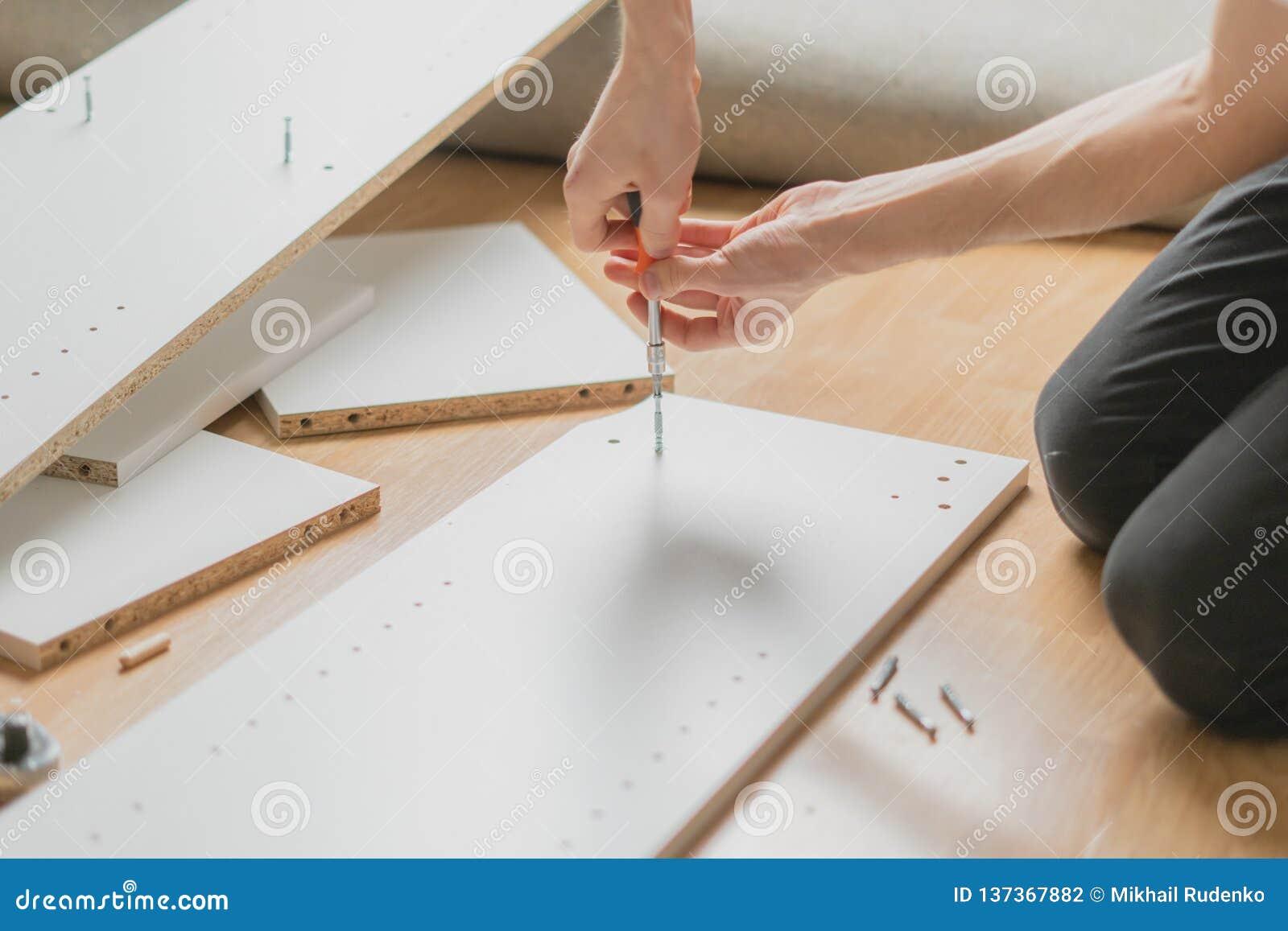Zamyka w górę mężczyzny gromadzić nowego meble z śrubokrętu b