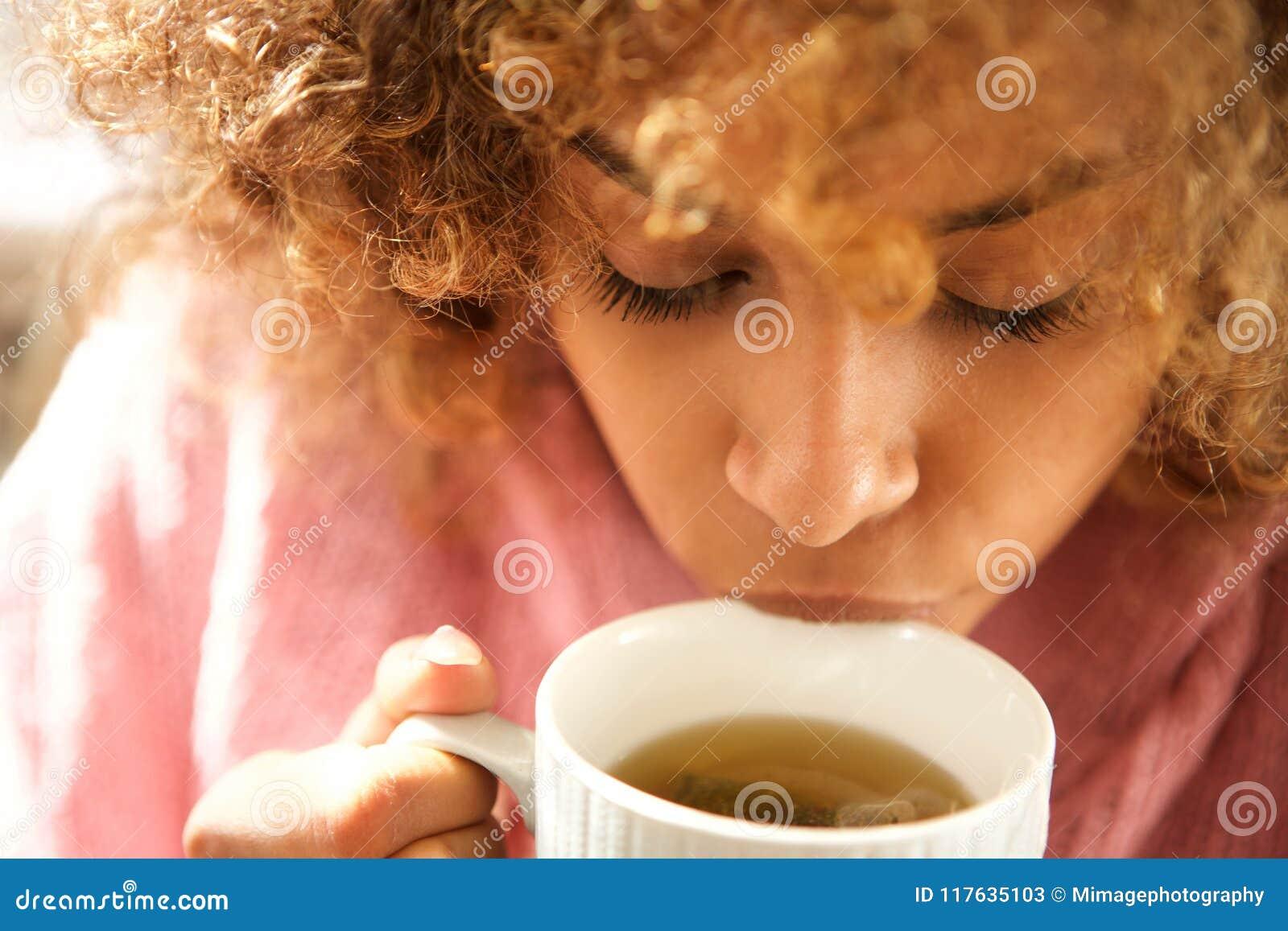 Zamyka w górę młodej murzynki pije filiżankę herbata