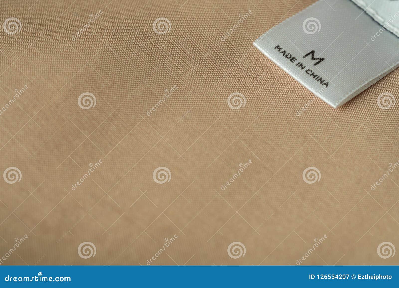 Zamyka w górę makro- strzału piszącego list robić w Chiny na t ubrania etykietka