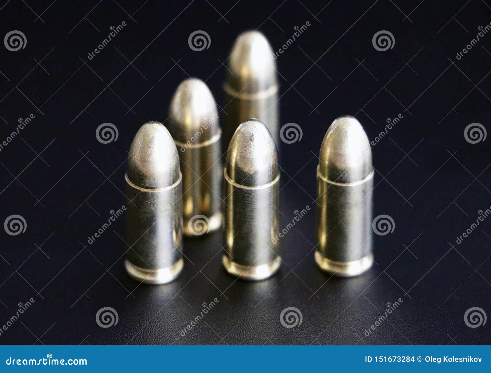 Zamyka w górę 9 mm złotego pistoletowego pociska ammo na tle