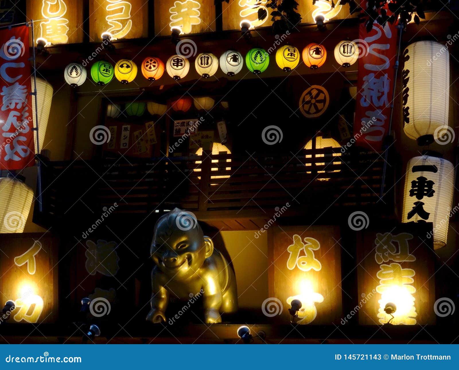 Zamyka w górę obrazka złota Billiken statua i signboards Japońska restauracja w Osaka