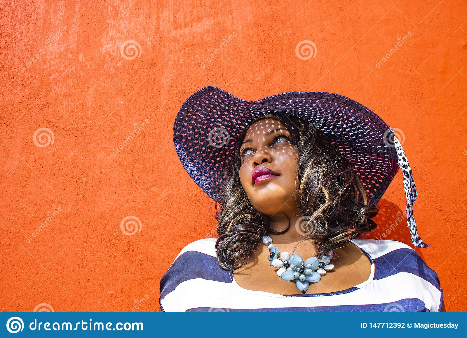 Zamyka w górę pięknej Afrykańskiej kobiety w błękitnej i białej pasiastej smokingowej modelacji przed tradycyjnym domem z pomarań