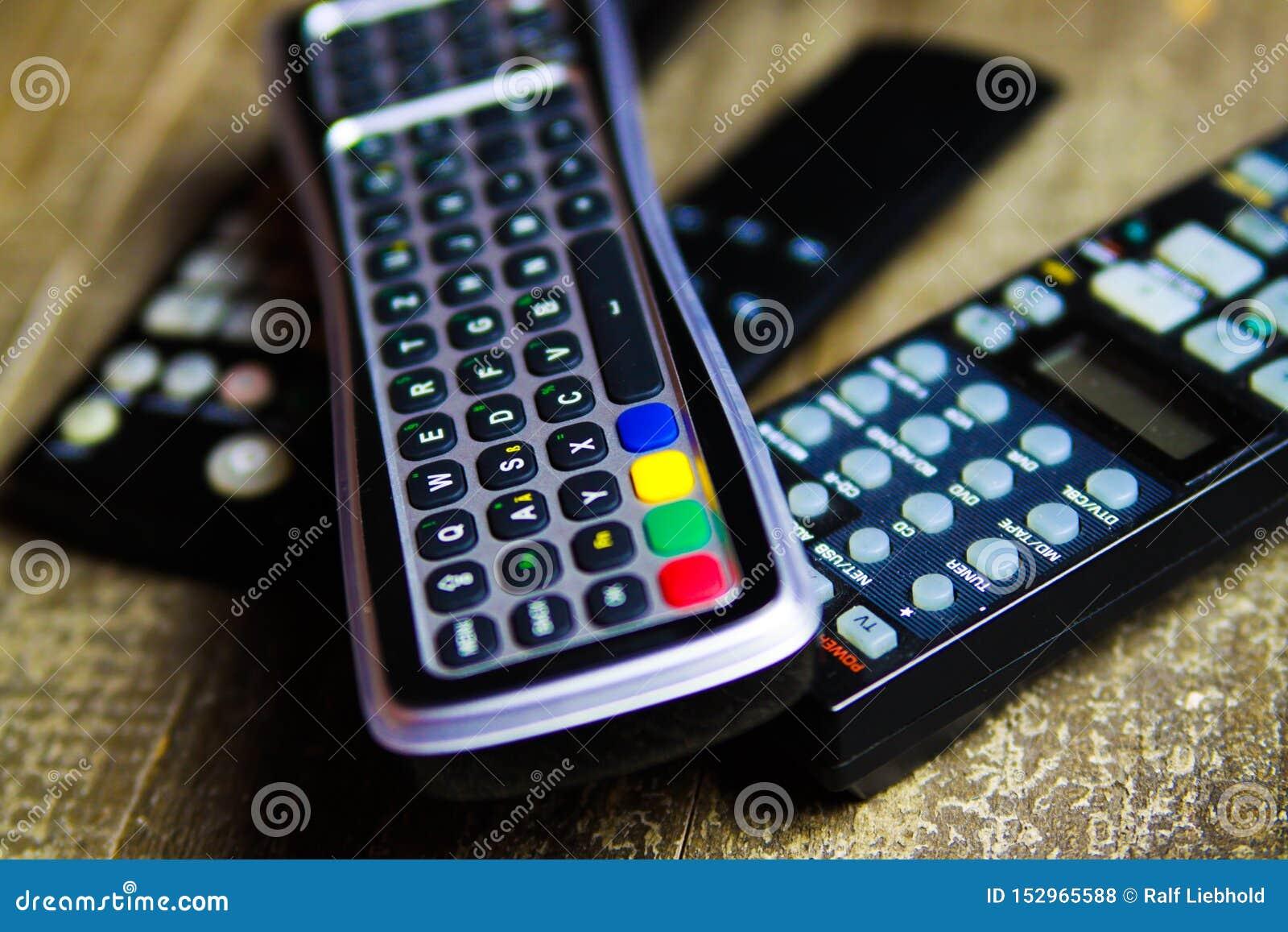 Zamyka w górę pilotów do tv dla TV, wideo i stereo muzyczny system na drewno stole