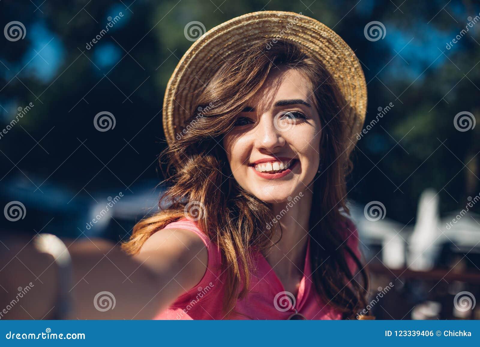 Zamyka w górę portret Ładnej roześmianej dziewczyny w kapeluszu robi selfie na plaży Śliczny lato mody portret piękno brunetki ko