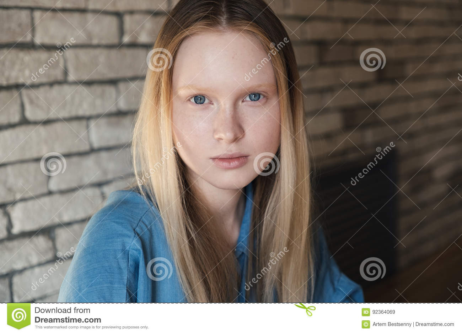 Zamyka w górę portreta młoda blondynki dziewczyna w błękitnej koszula