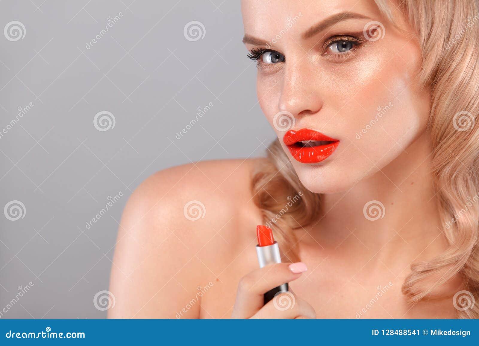 Zamyka w górę portreta rouging jej wargi atrakcyjna dziewczyna Trzyma czerwoną pomadkę w myszy Odizolowywający na szarość