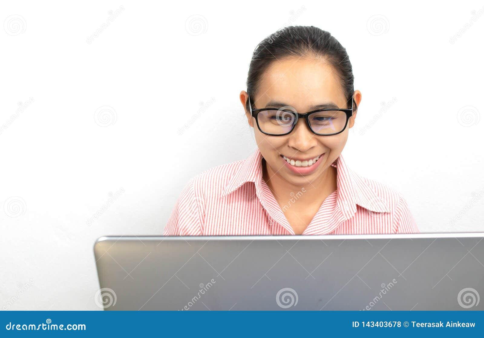 Zamyka w górę portreta szczęśliwa Azjatycka kobieta, jest ubranym szkła pracuje z laptopem w pokoju z przyglądającą smily twarzą,