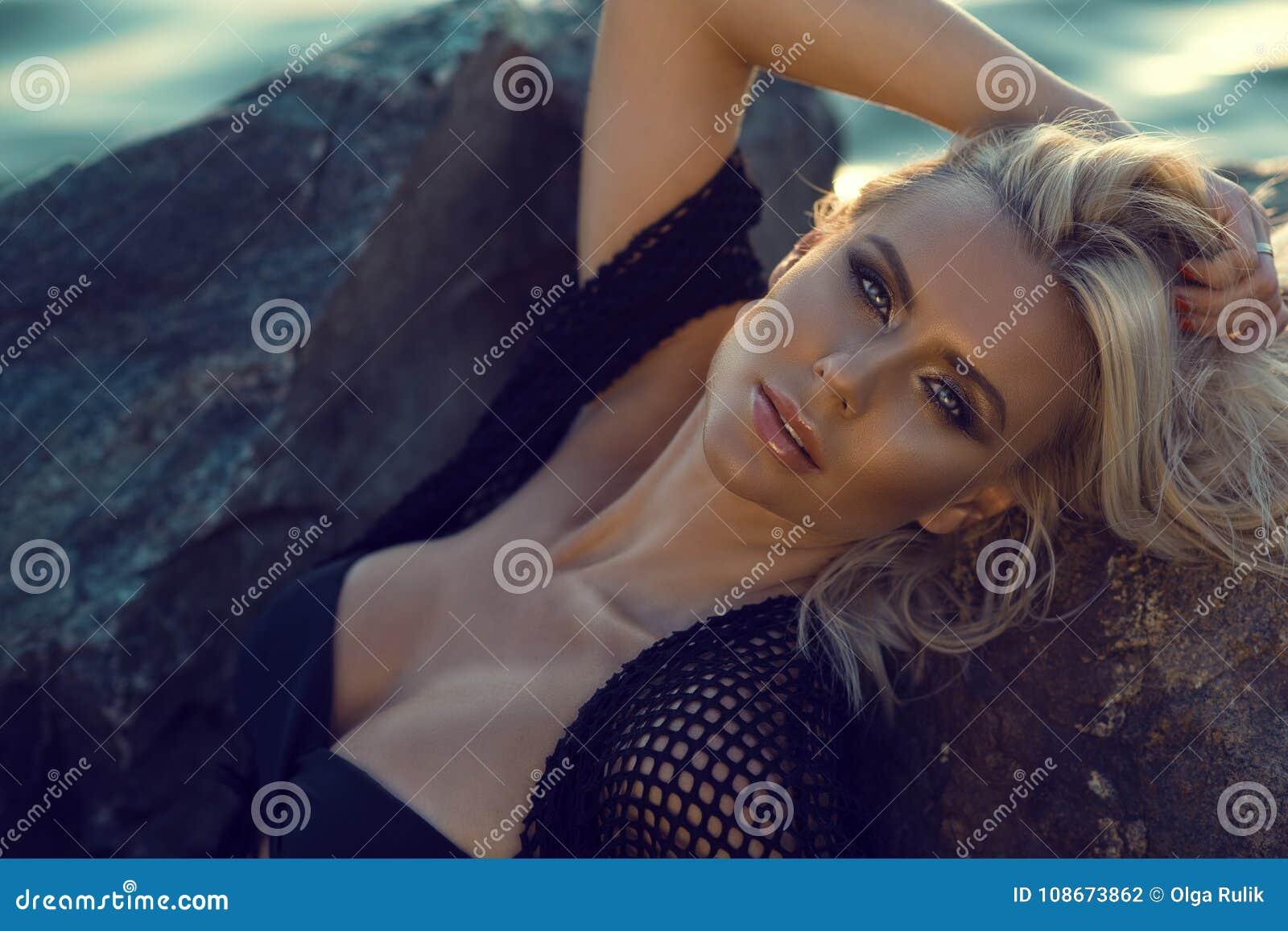Zamyka w górę portreta wspaniały glam garbnikująca blond kobieta jest ubranym czarną swimsuit i lata tunikę relaksuje na kamienia
