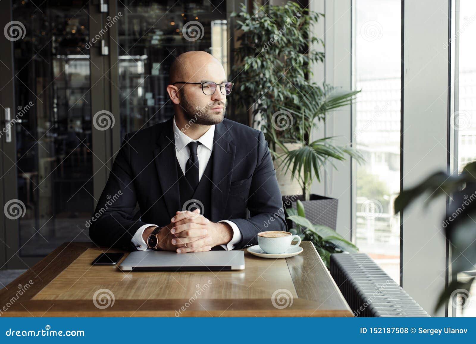 Zamyka w górę przystojnego biznesmena, pracujący na laptopie w restauracji