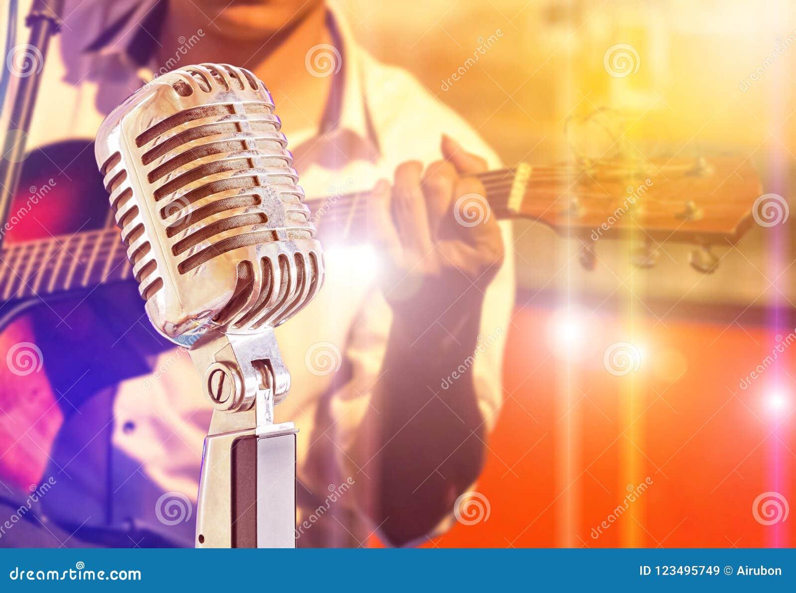 Zamyka w górę retro mikrofonu z muzykiem bawić się gitarę akustyczną na zespole