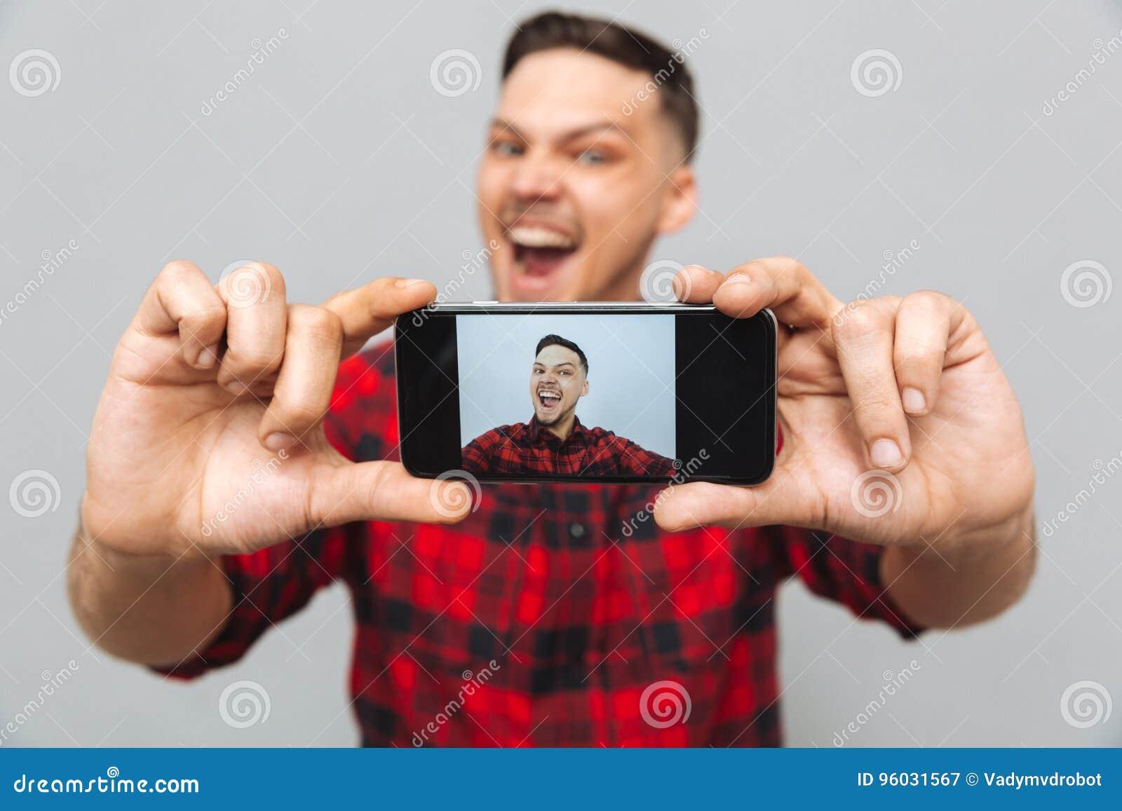 Zamyka w górę wizerunku robi fotografii na smartphone szczęśliwy mężczyzna