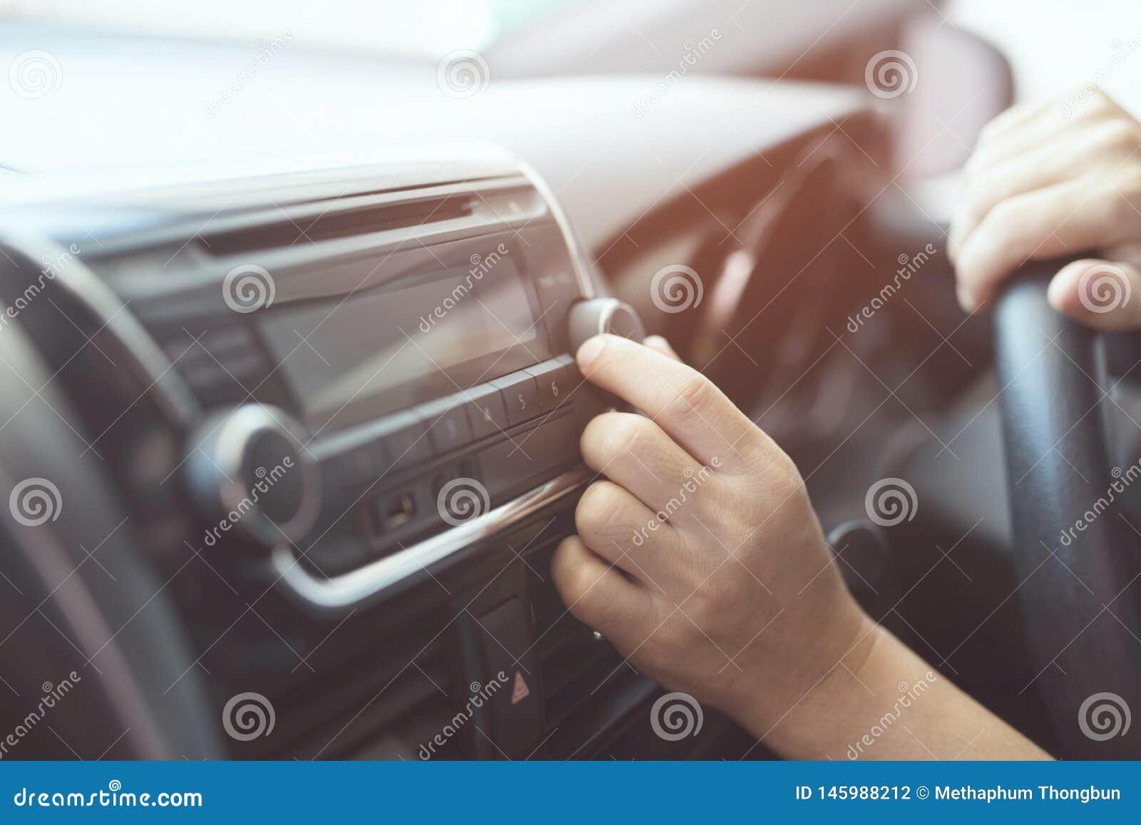 Zamyka w g?r? r?ki samochodowego radia otwartego s?uchania Kierowcy odmieniania kr?cenia guzika radia stacje