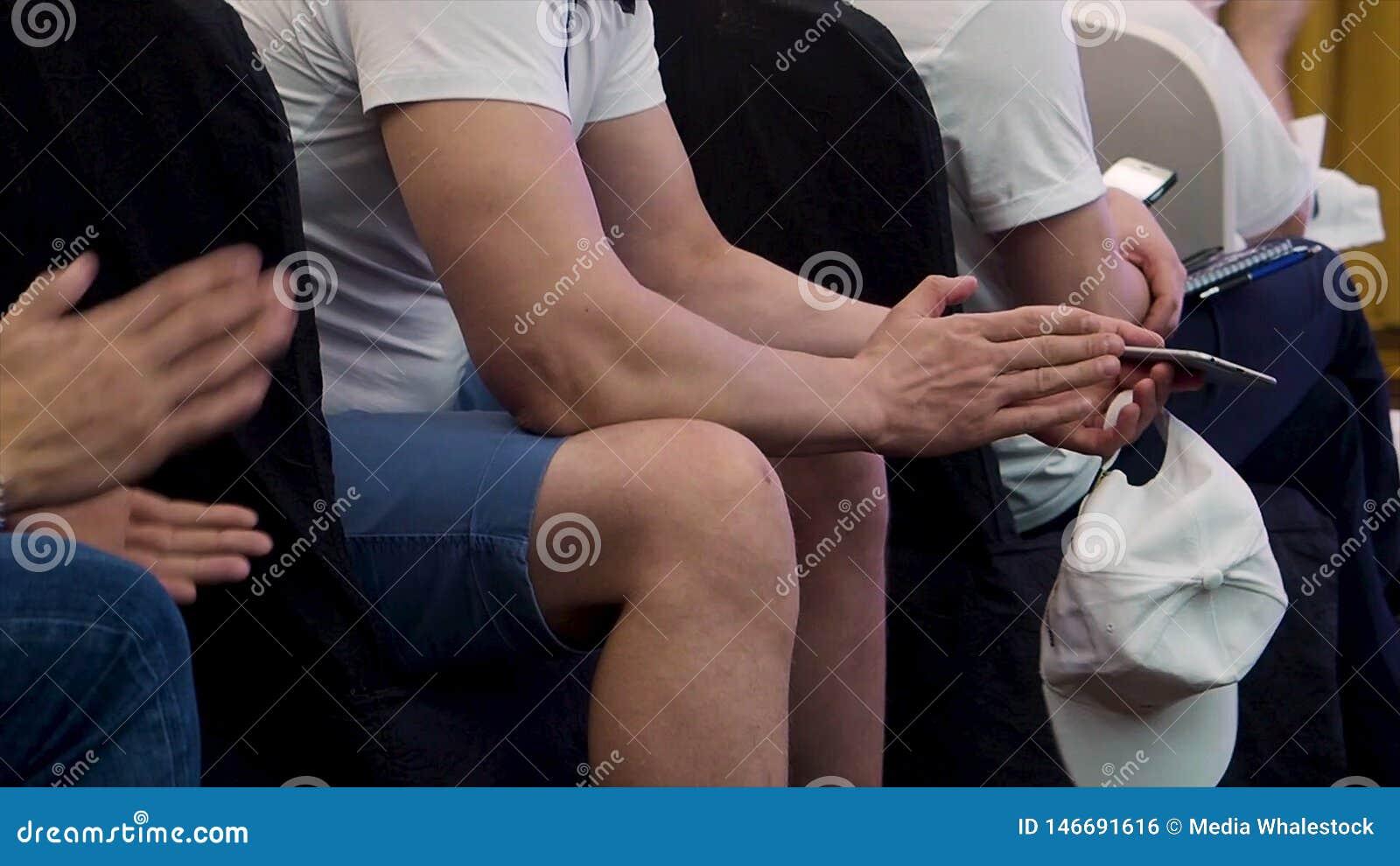 Zamyka w g?r? ludzi siedzi z rz?du i oklaskuje przy konferencj? dla zapas M??czyzna w drelichu zwiera trzyma? jego smartphone