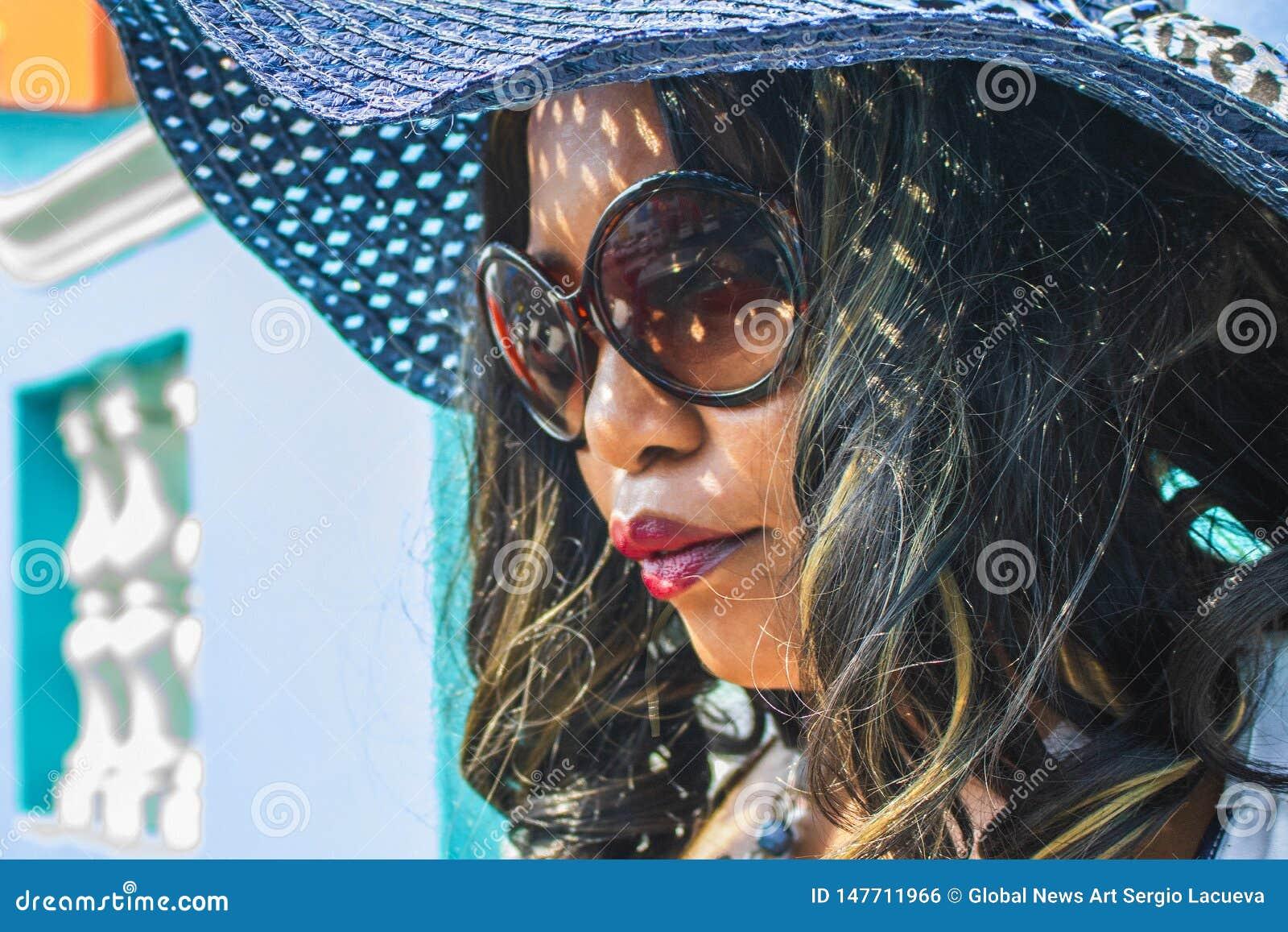 Zamyka w g?r? pi?knej Afryka?skiej kobiety w b??kitnej i bia?ej pasiastej smokingowej modelacji przed tradycyjnymi bo domami z or