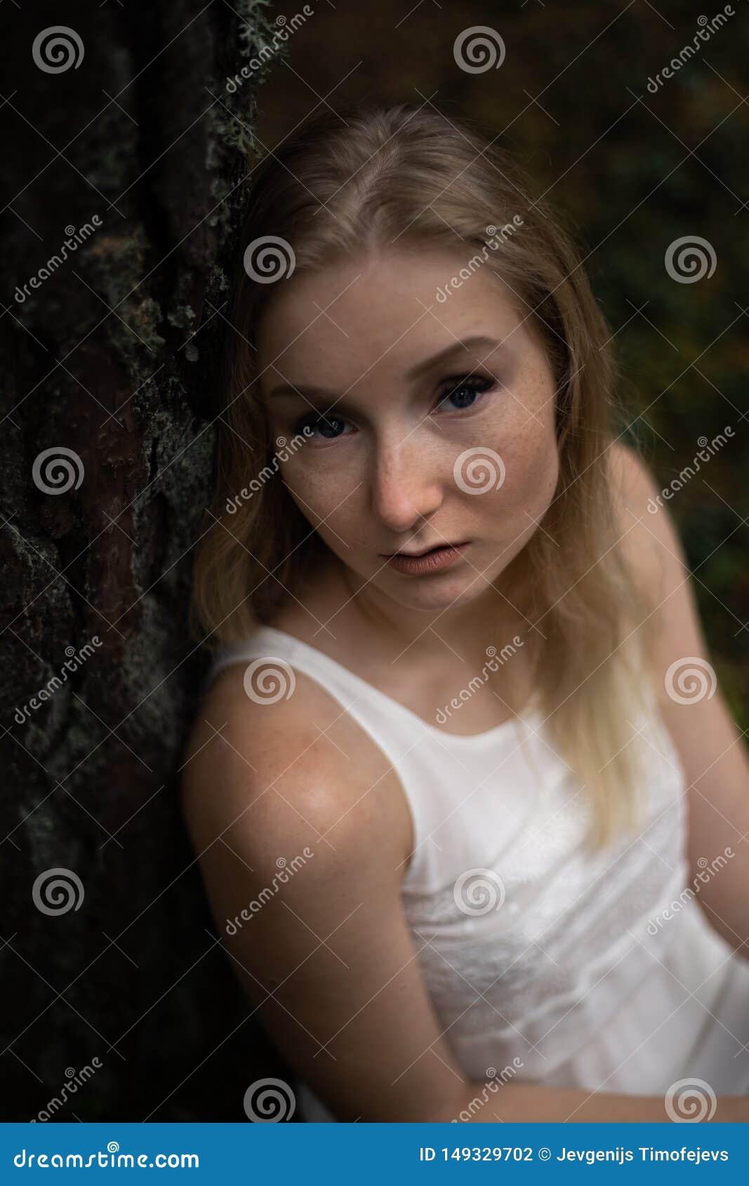 Zamyka w g?r? portreta - Pi?knej m?odej blondynki kobiety lasowa boginka w biel sukni w wiecznozielonym drewnie