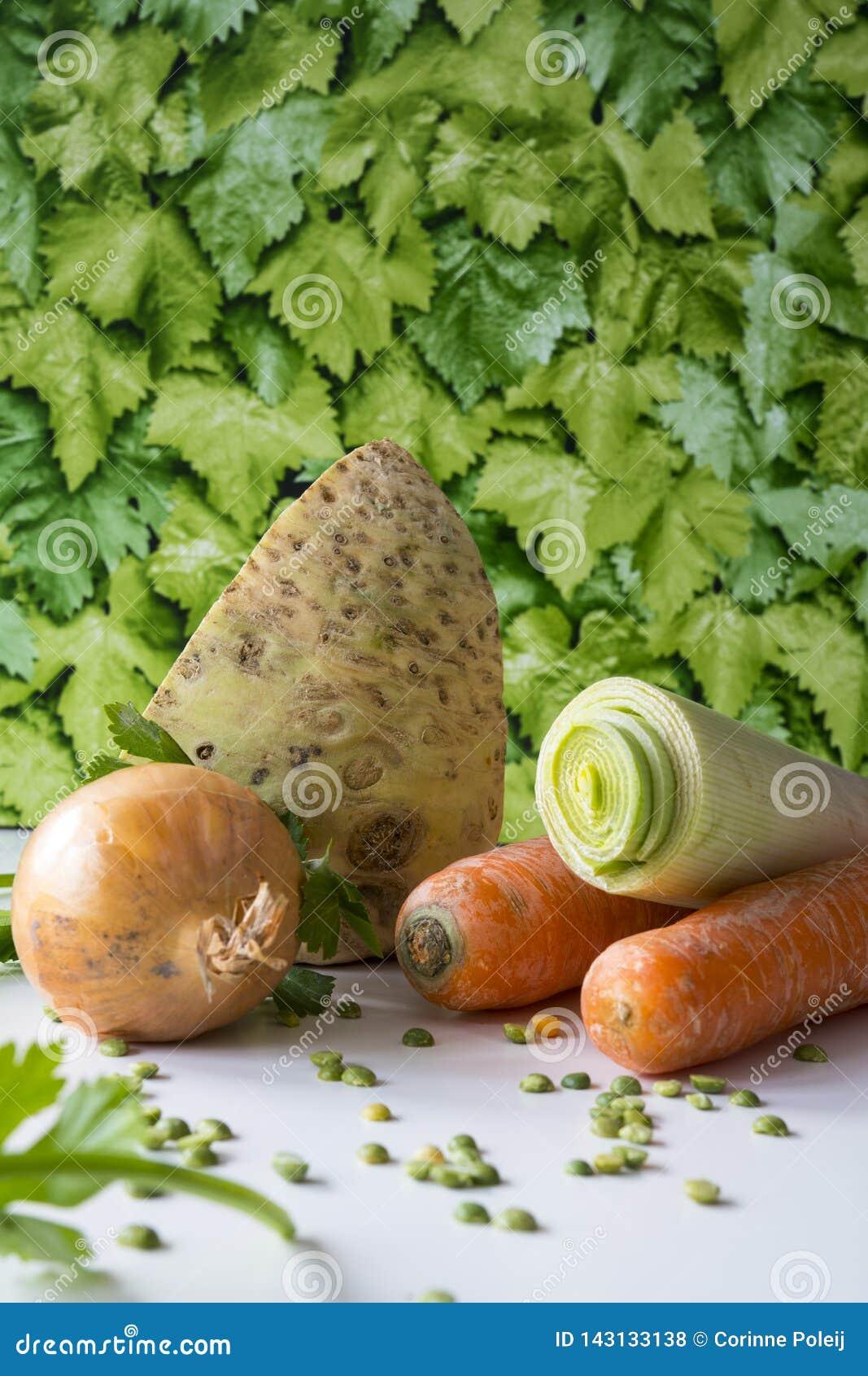 Zanahorias, unión, puerro, perejil, guisantes partidos en la tabla blanca, backgrund verde de las hojas