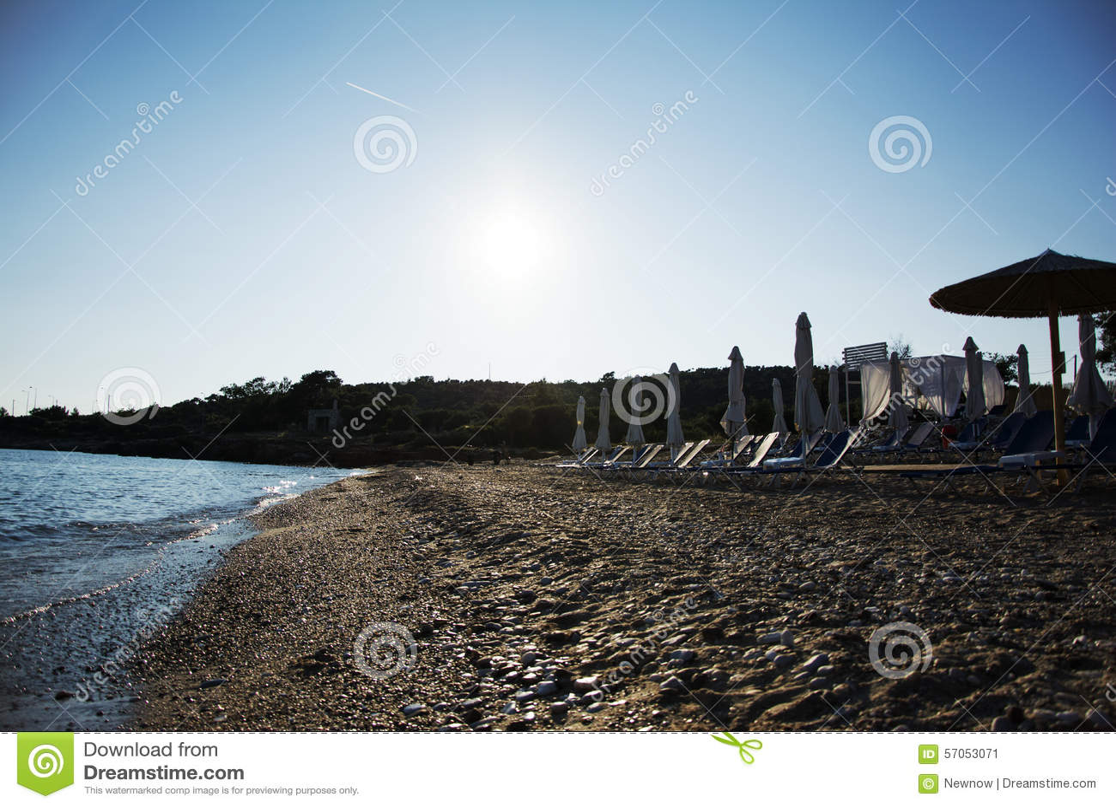 Zandig en pebbled strand in de zonsondergang