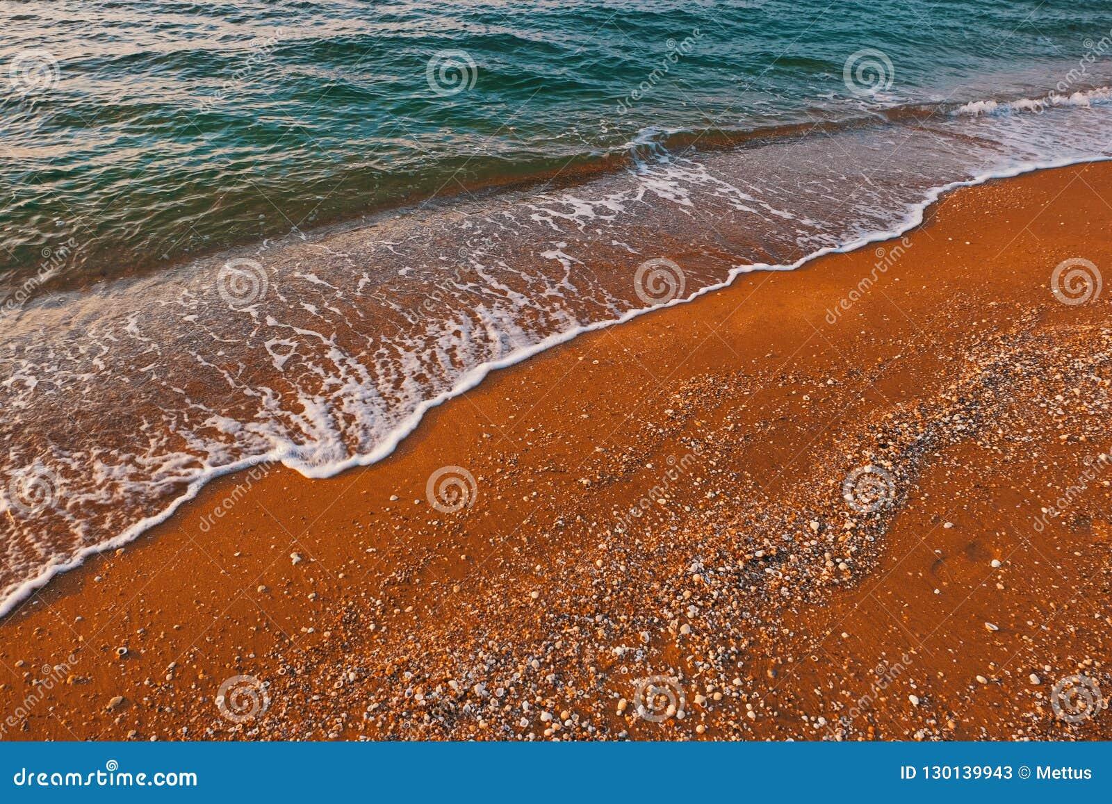 Zandige zeekust met zachte golf