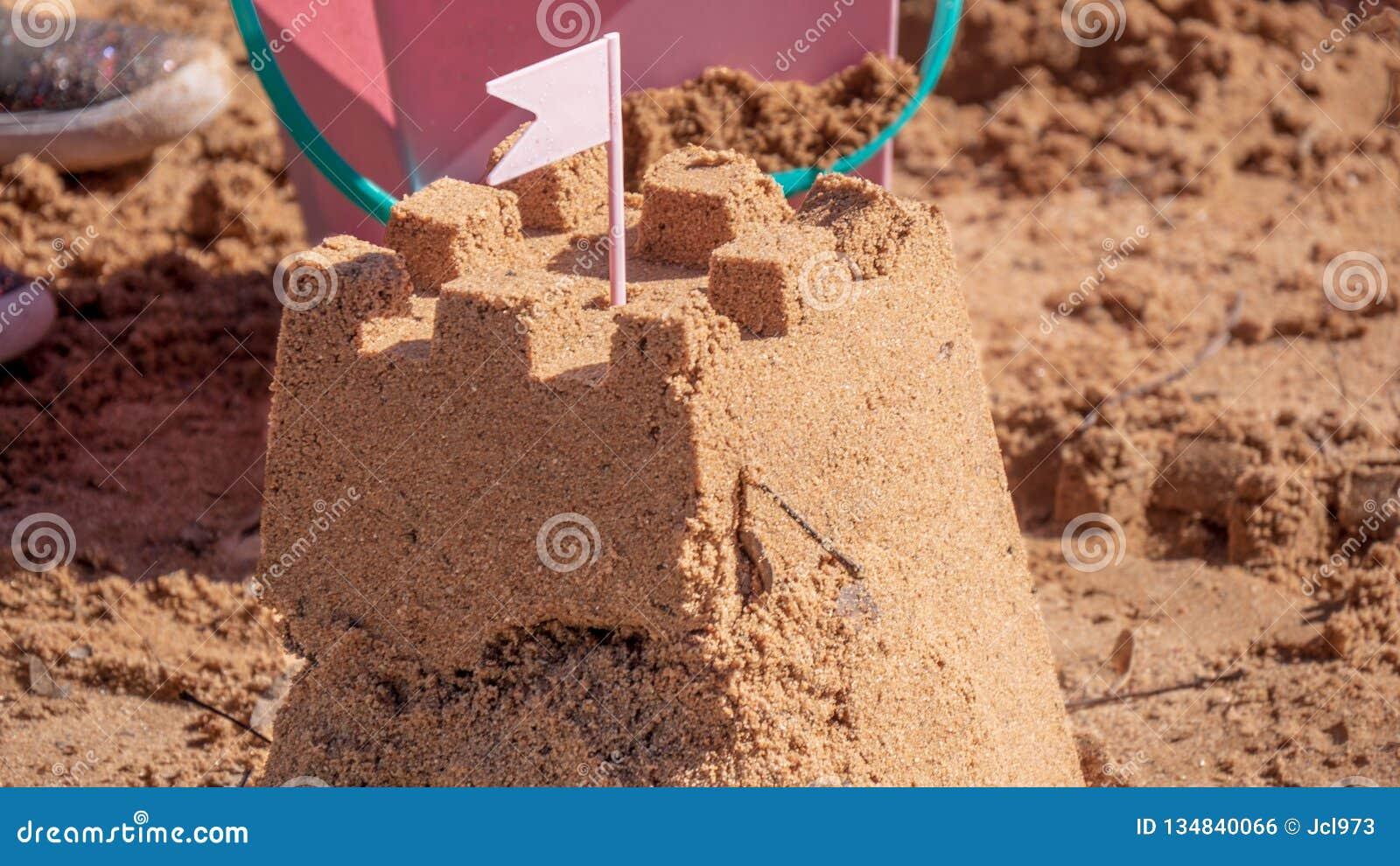 Zandkasteel door strandspeelgoed dat wordt omringd