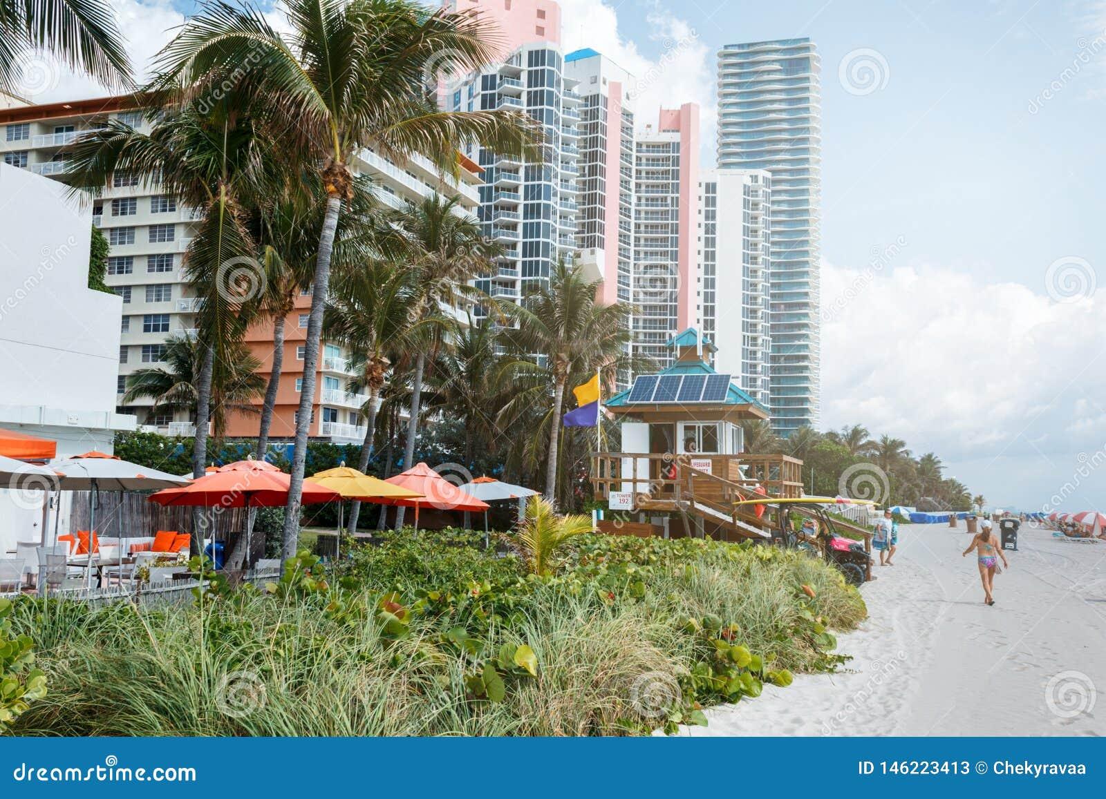 Zandstrand de blauwe hemel in van Miami, de Atlantische Oceaan, palmen, wolkenkrabber bij de achtergrond