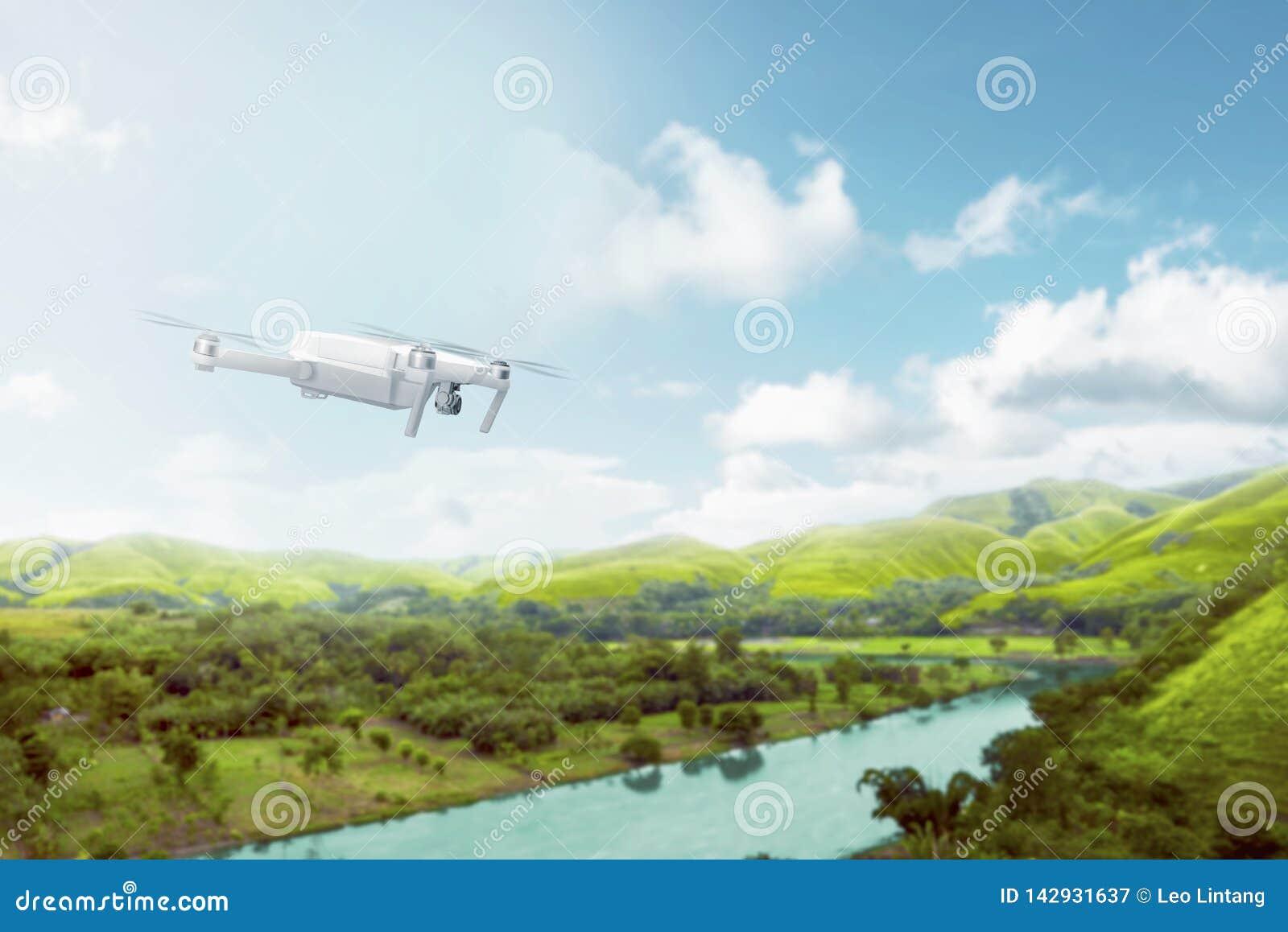 Zangão branco com voo da câmera sobre montes verdes com rio e árvores