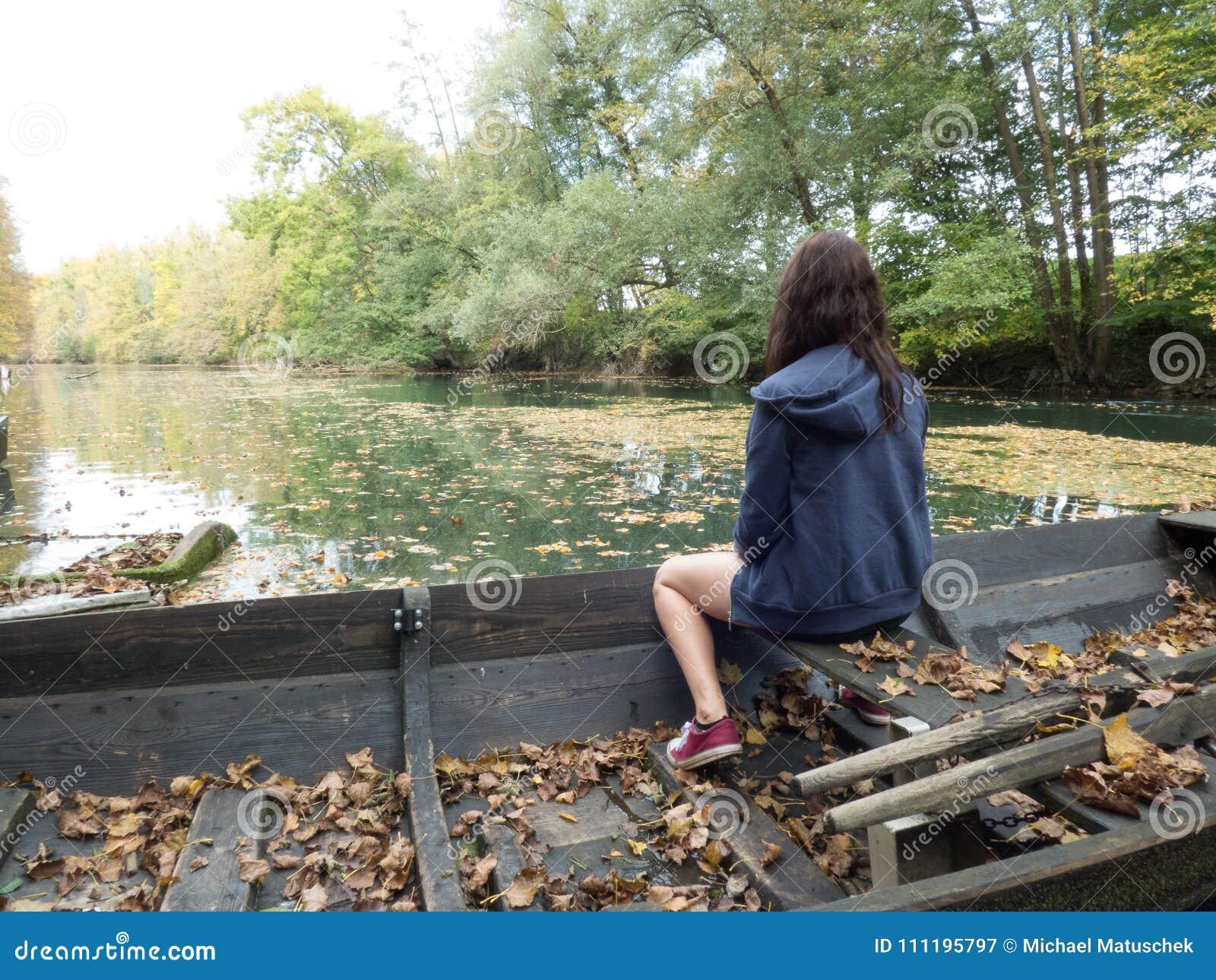 Zaniechane łodzie kłaść out na rzece z kobietami siedzi na one