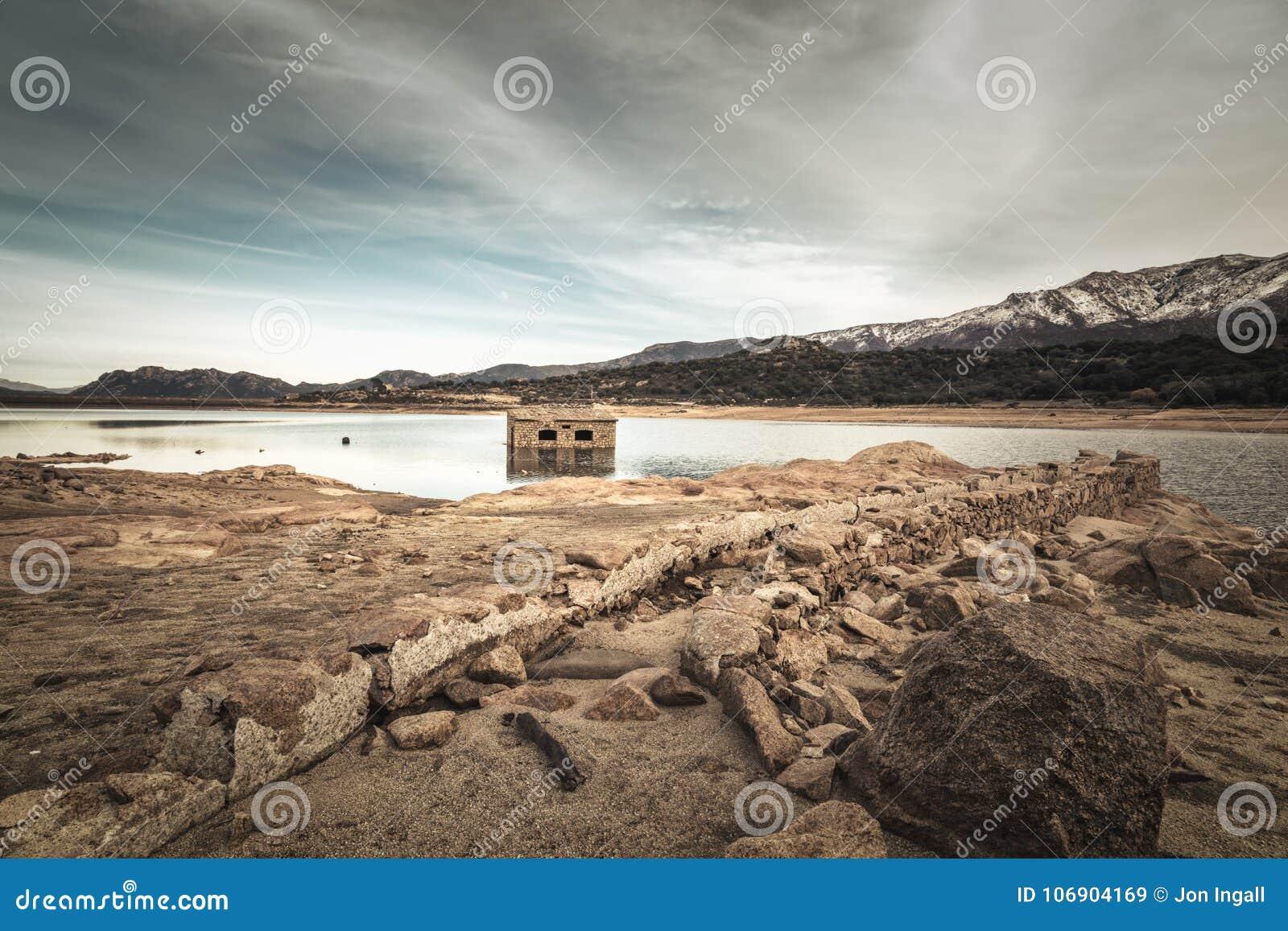 Zaniechany i stronniczo zanurzający kamienny budynek w jeziorze w Cors