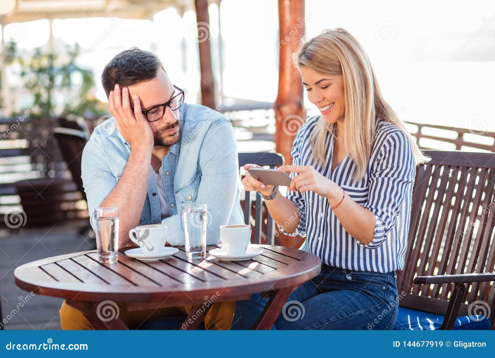 Zanudzający młody człowiek czekać na jego dziewczyny zatrzymywać używać telefon