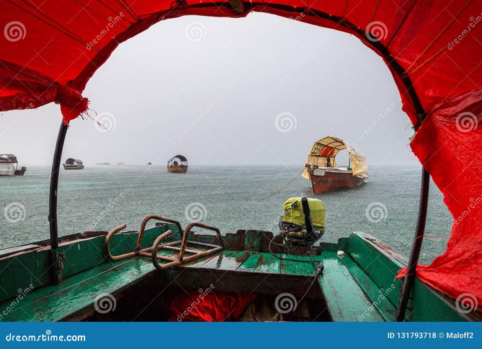 Zanzibar regnig säsong Inom ett traditionellt fartyg under duschregn på redden nära fängelseön stenstad, Unguja, Tanzania