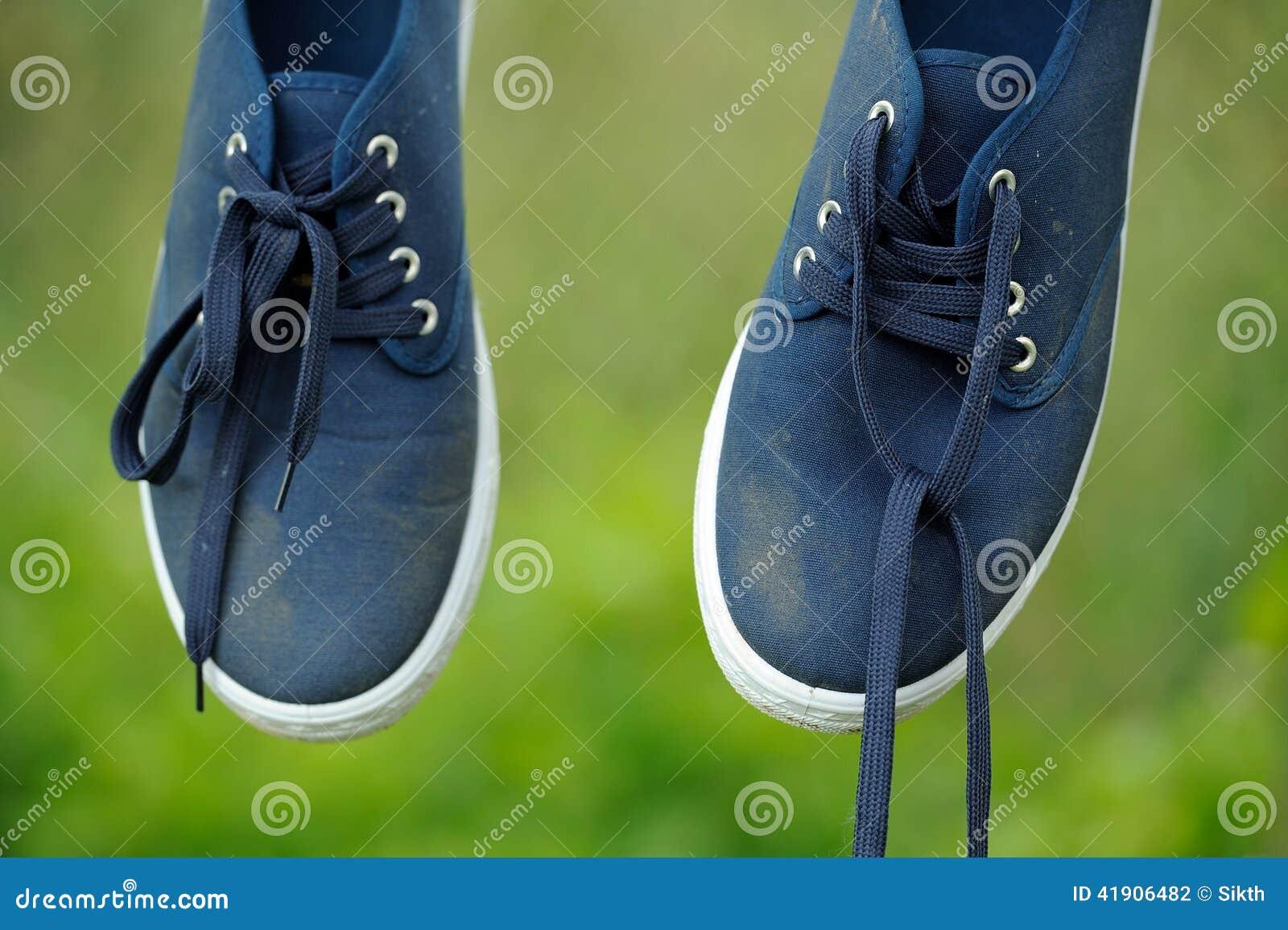 Zapatillas de deporte azules sucias en línea de ropa