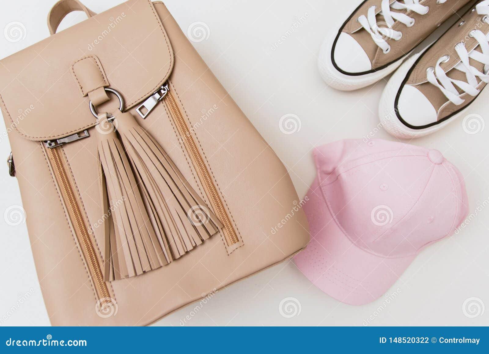Zapatillas de deporte beige, mochila y casquillo rosado en fondo ligero en colores pastel