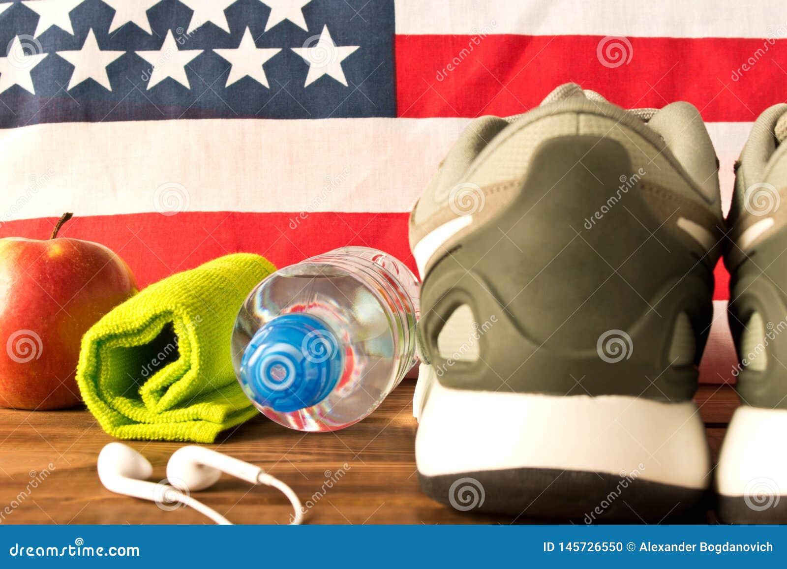 Zapatillas de deporte y accesorios grises de la aptitud en el fondo de la bandera americana El concepto de la salud de la naci?n