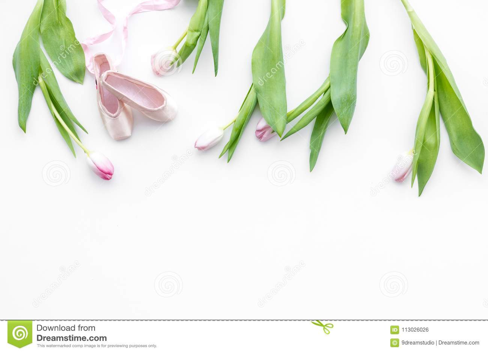 Zapatos de ballet cerca de las flores delicadas en el espacio blanco de la copia de la opinión superior del fondo