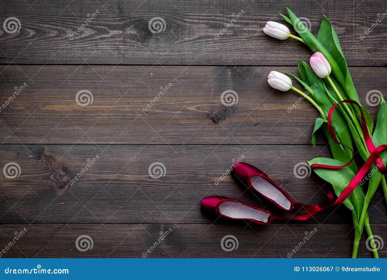 Zapatos de ballet cerca de las flores delicadas en espacio de madera oscuro de la copia de la opinión superior del fondo
