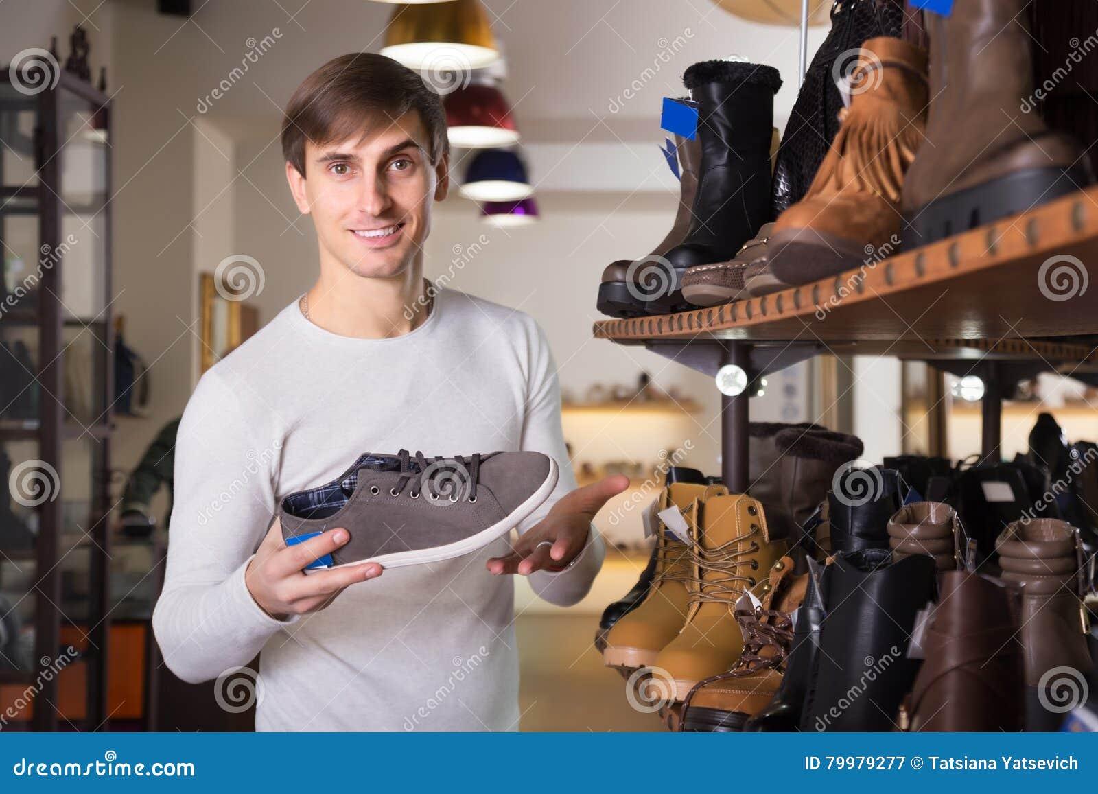 Zapatos de compra del verano del hombre joven