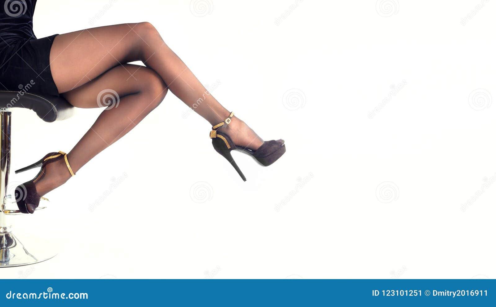 8b85c3063074 Zapatos de los tacones altos de la mujer que llevan atractiva y falda corta  que se sientan en silla de la oficina Aislado en blanco