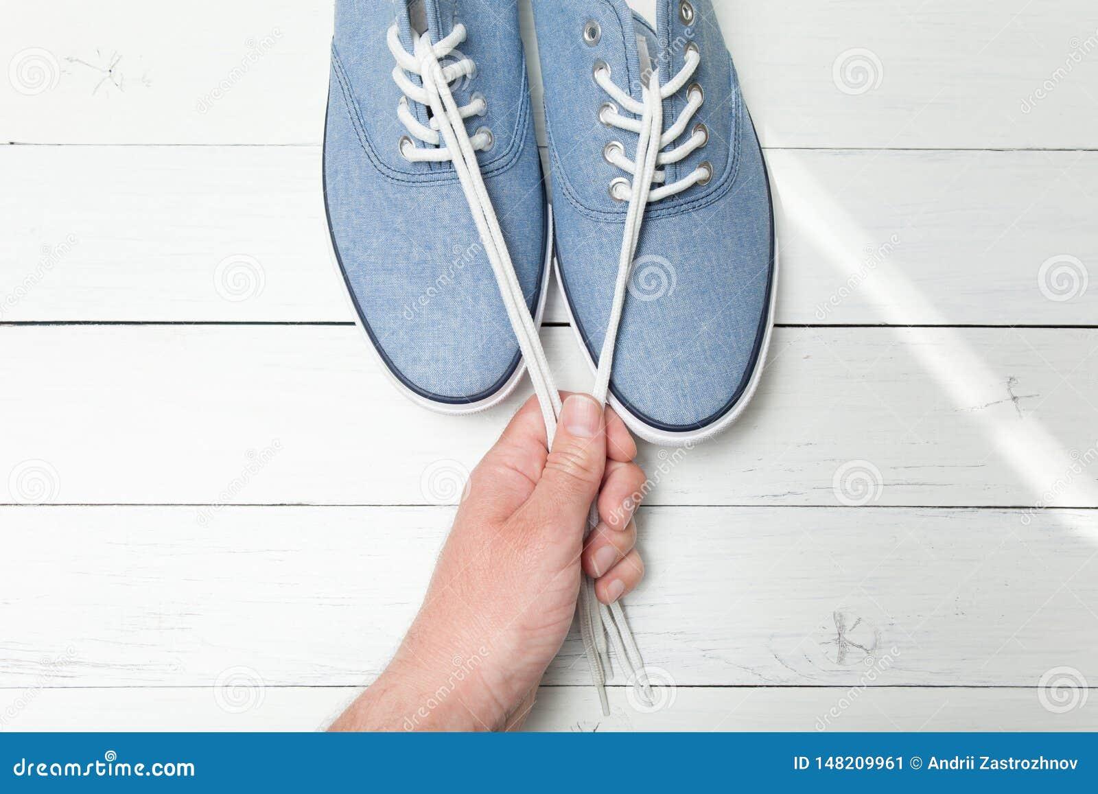 Zapatos de moda en un fondo de madera ligero, cordones blancos en una mano