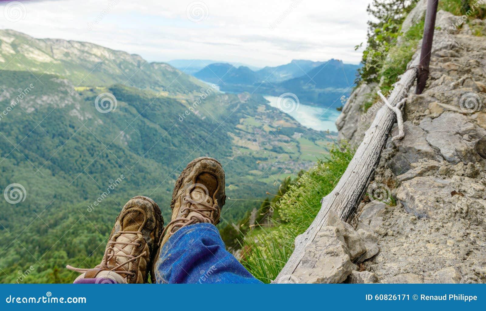 Zapatos del Backpacker en el borde de un rastro, lago en el fondo