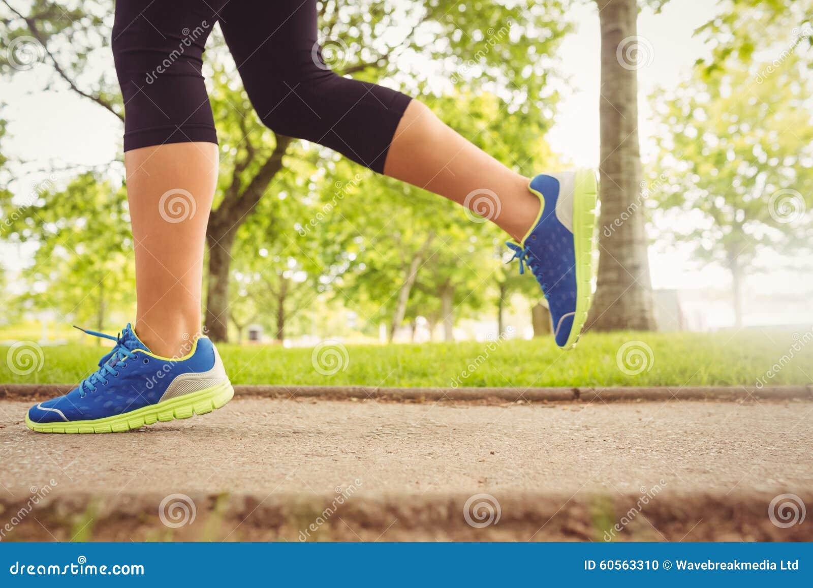 Zapatos del deporte de la mujer que llevan que activan en parque