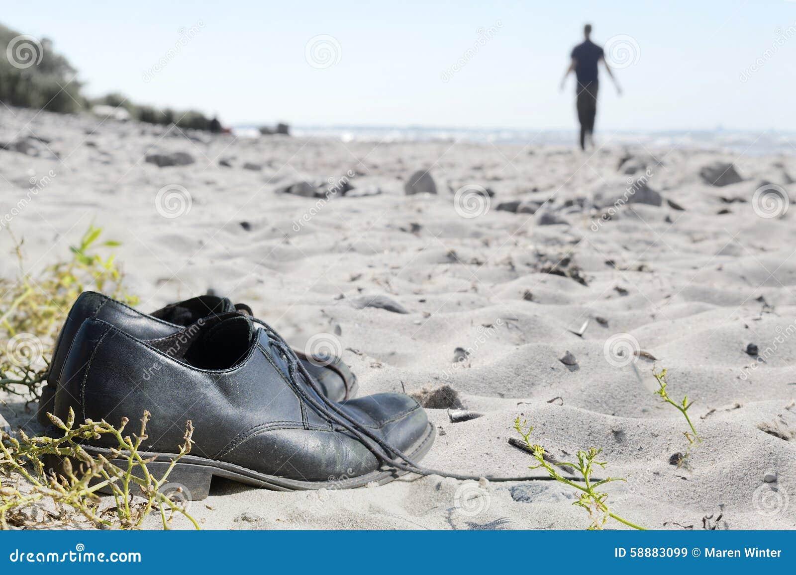Zapatos del negocio en la playa y un hombre borroso que se va al th
