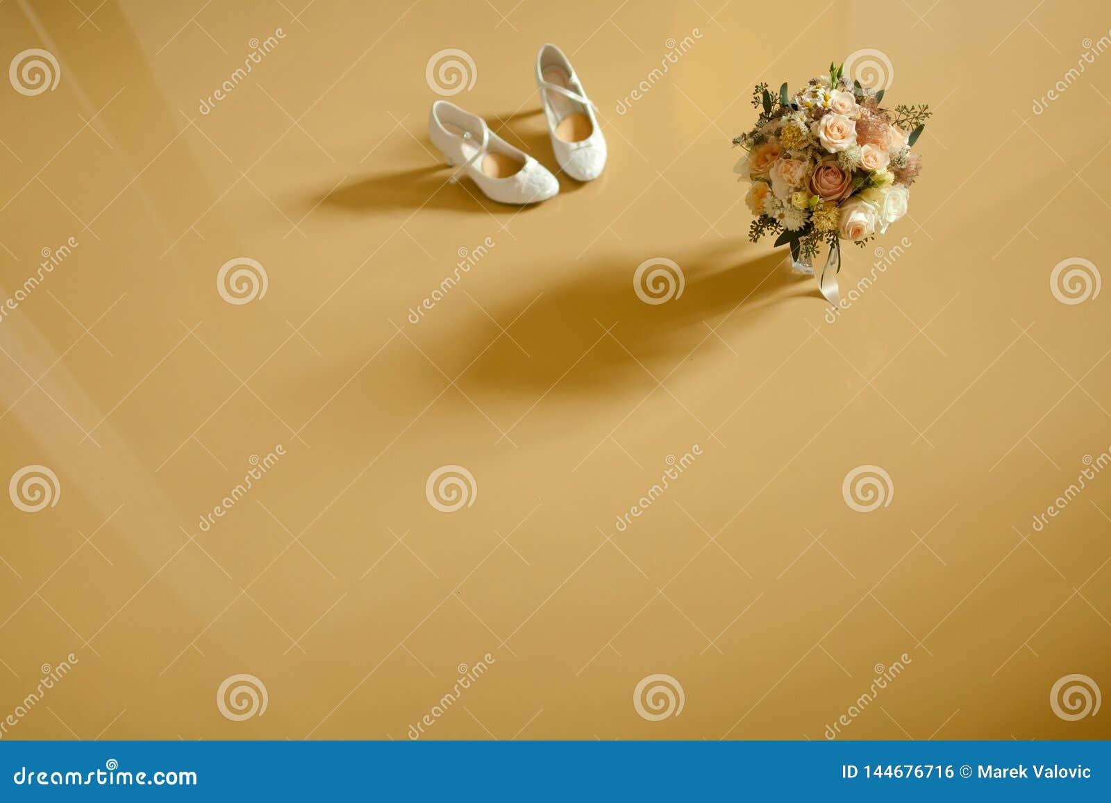 Zapatos del ramo y de la boda en el piso amarillo capturado de la visión superior