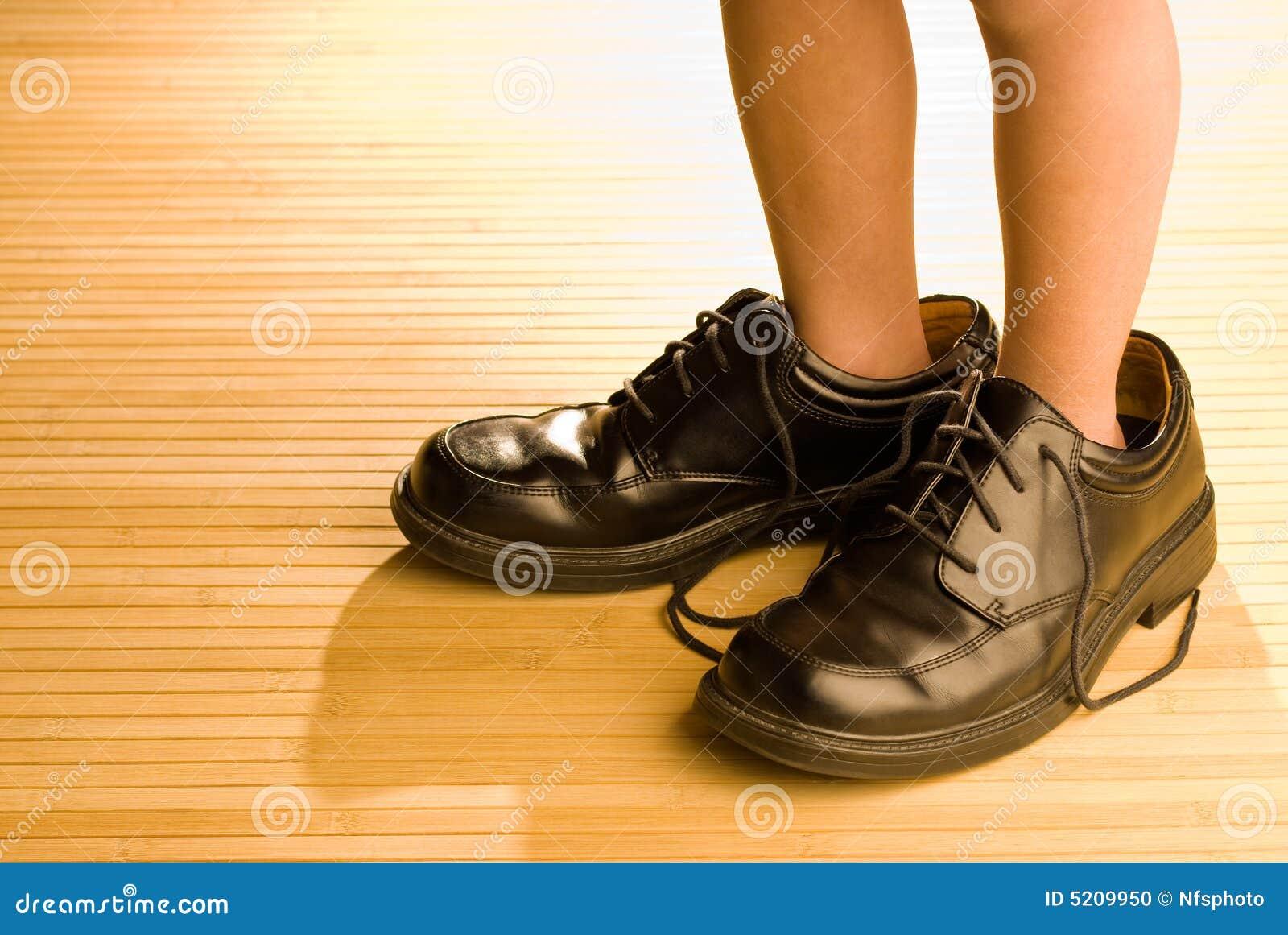 Zapatos grandes a llenar, pies del niño en zapatos negros grandes