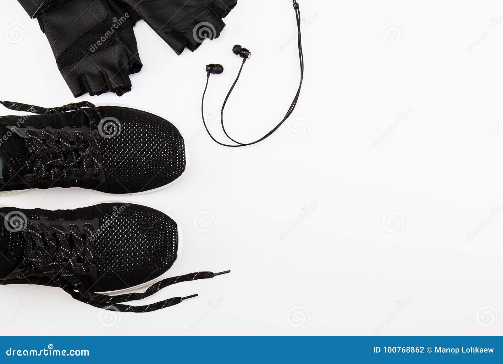 Zapatos, guante y auricular negros del deporte en el fondo blanco