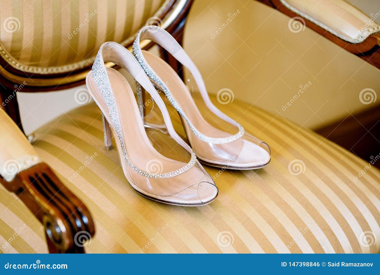 Zapatos nupciales en una silla con una tapicería de oro y manijas de madera